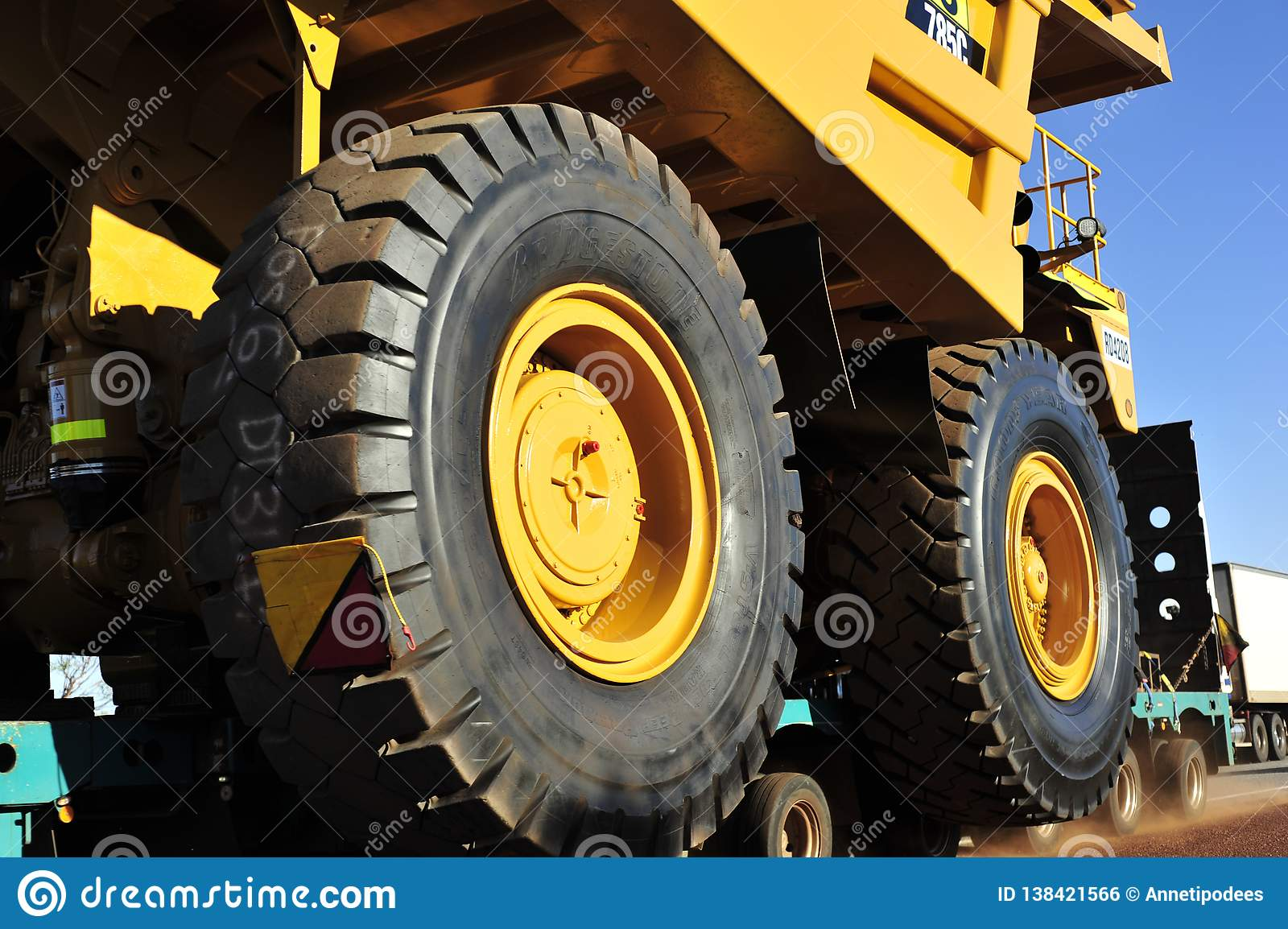 Close up of the Huge Ore Carrier Tyre as it Passes, with the Other Truck Passing on the Left.