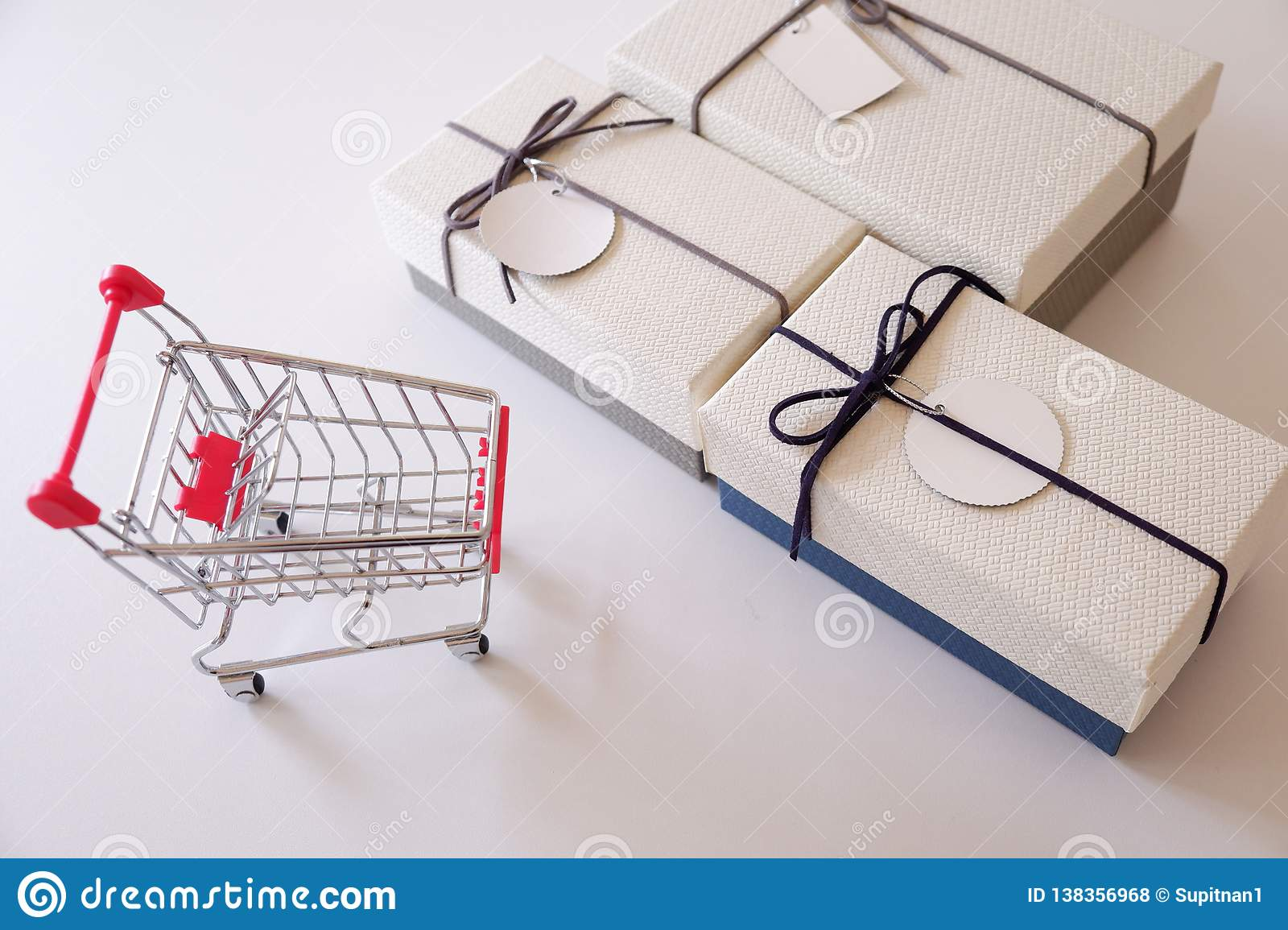 Close-up of gift boxes and shopping cart on white desk