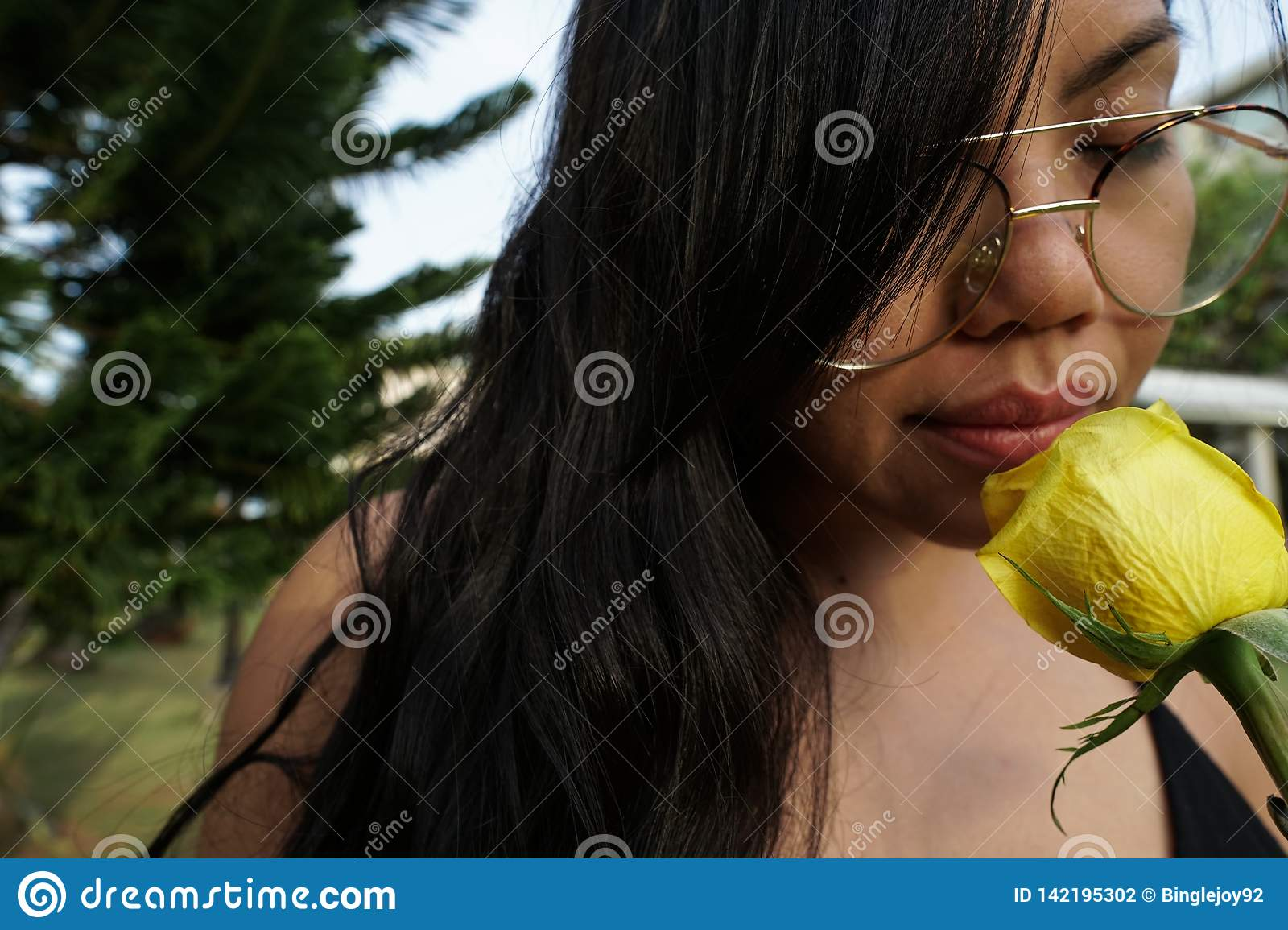 Close-up of girl with glasses, holding yellow rose flower.