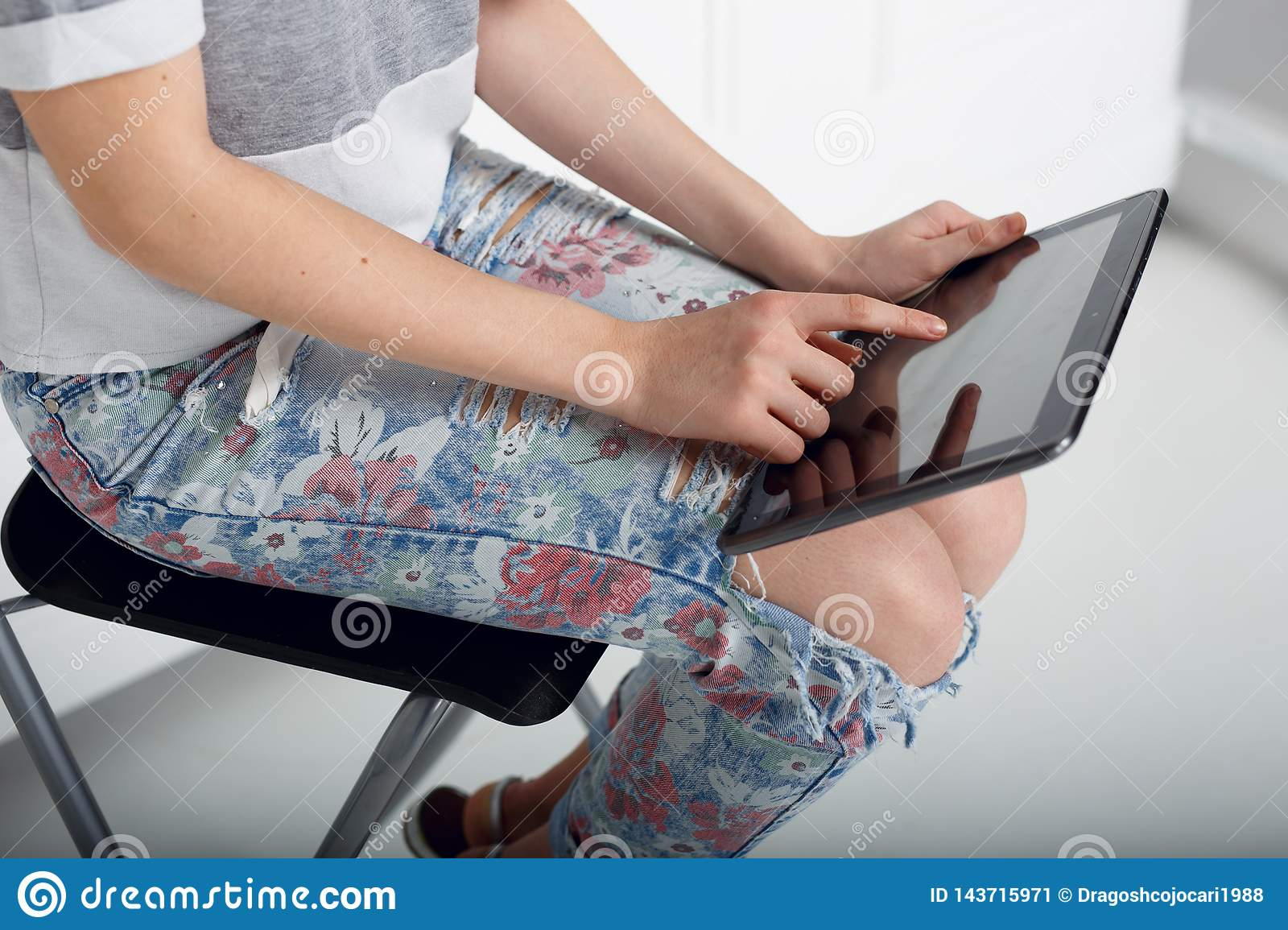 Close up of a girl holding on his knee a tablet and touch the screen with finger. Hand presses on screen digital tablet.