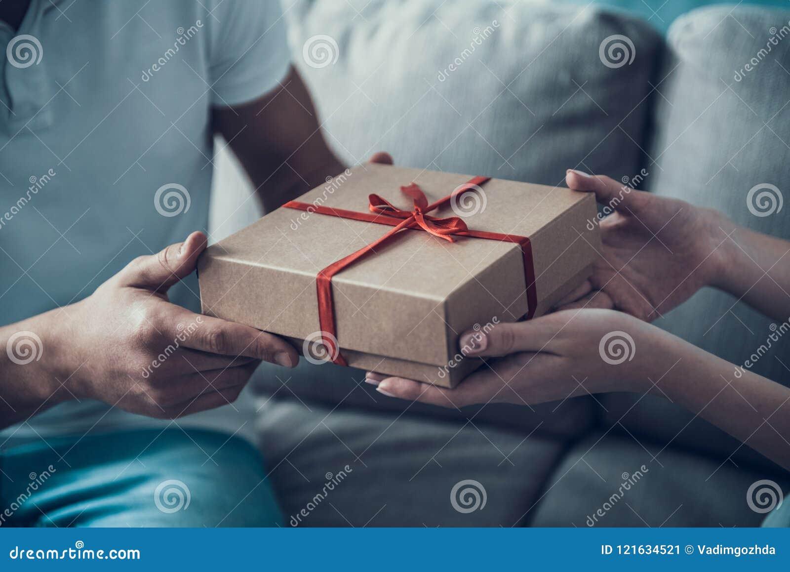 Girlfriend Giving Gift Box To Boyfriend