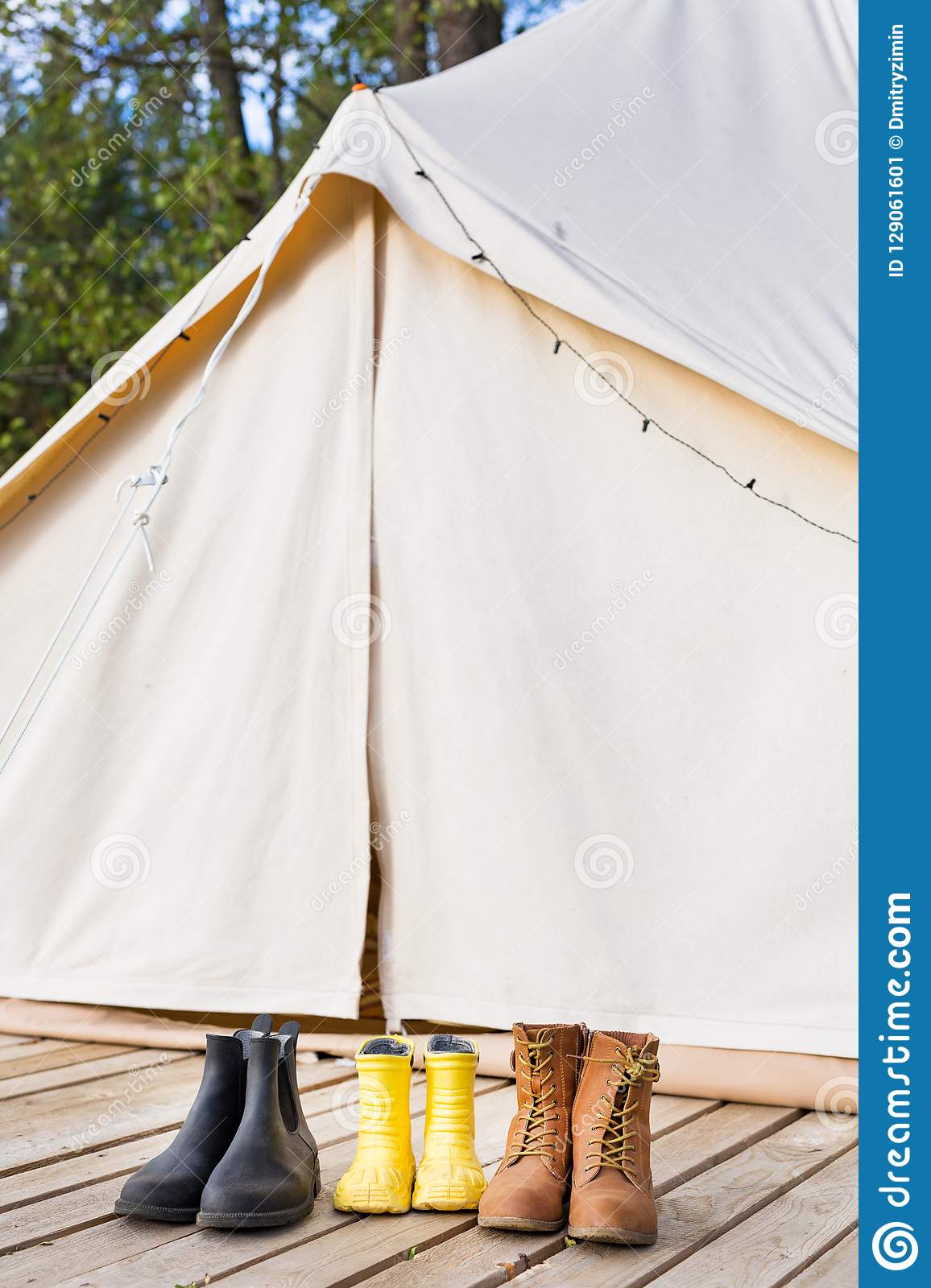Close-up of glamping bell tent with shoes. Family camping concept
