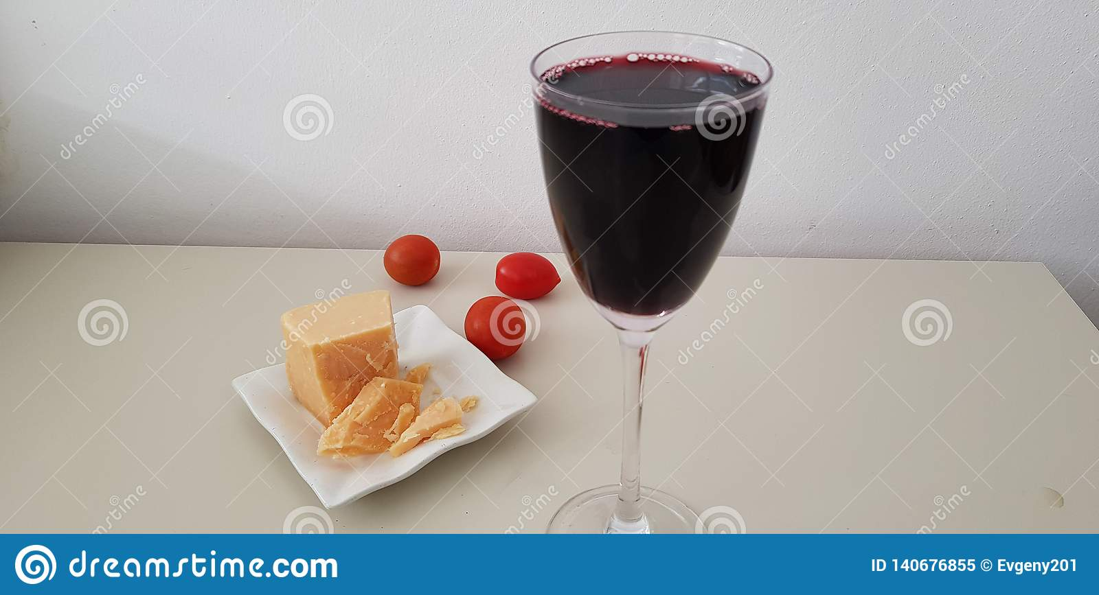 Close up of glass of red vine on white table