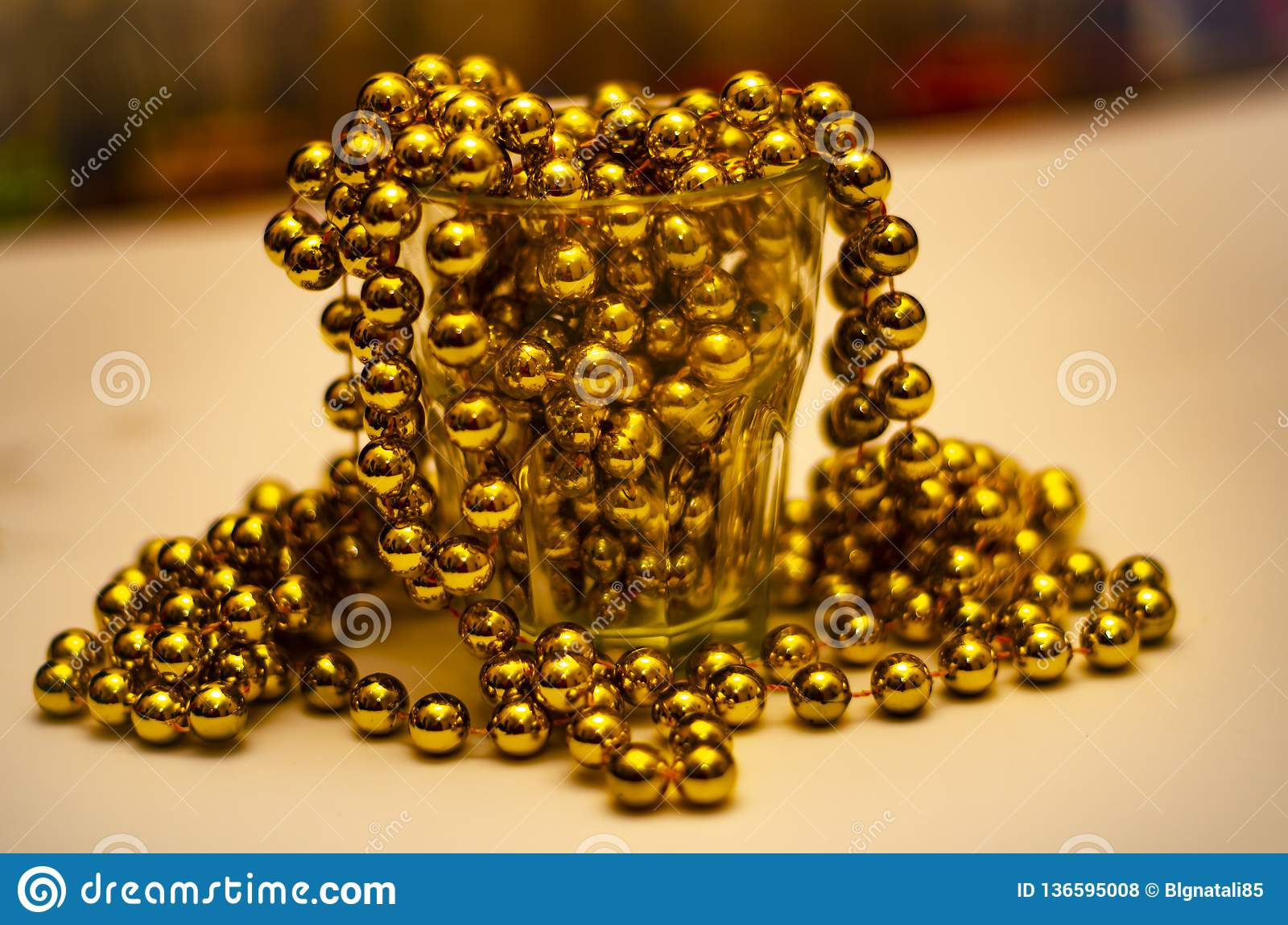Close-up of gold beads in a glass with a color bottom with a soft blurred background