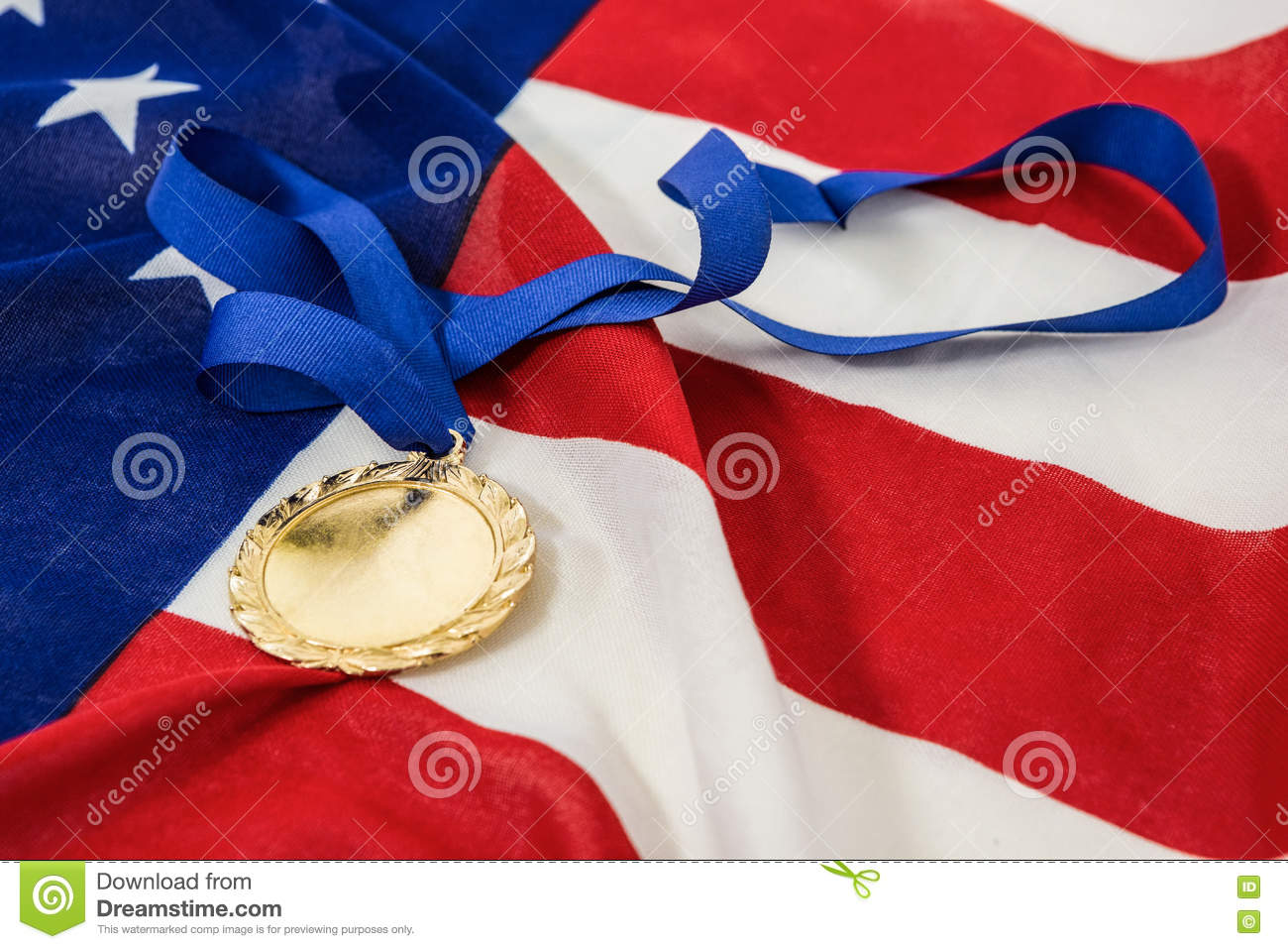 Close-up of gold medal on american flag