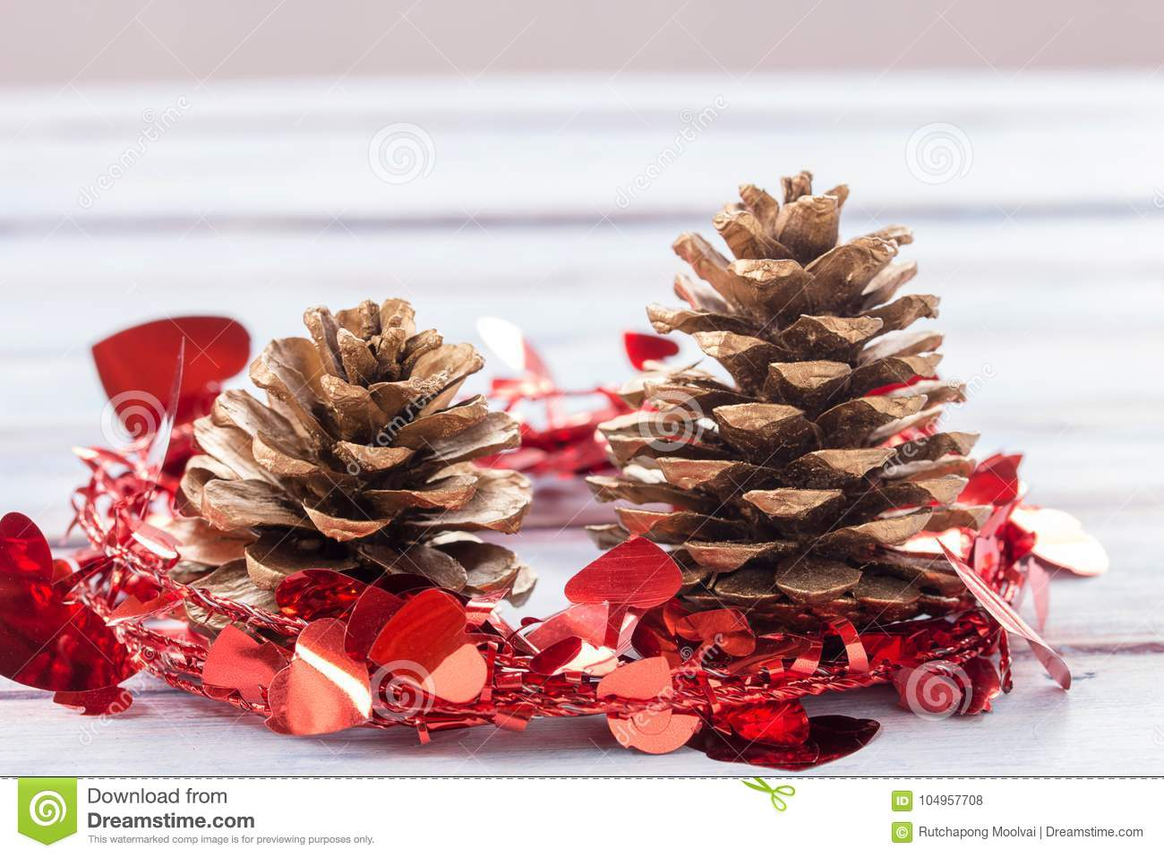Close up gold pine cones and christmas decoration on a white woo
