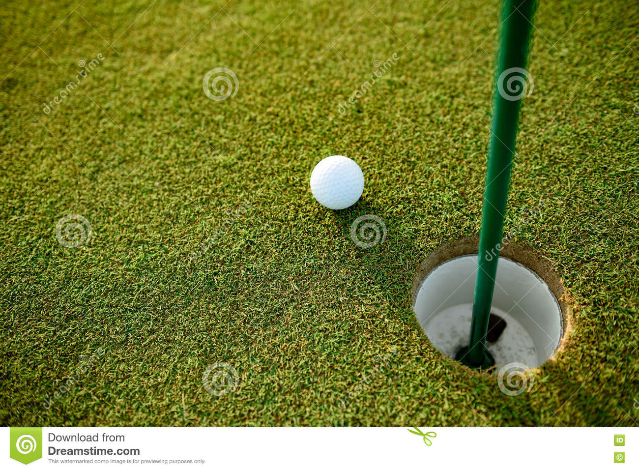 close up of golf ball next to hole stock photo image 72850790