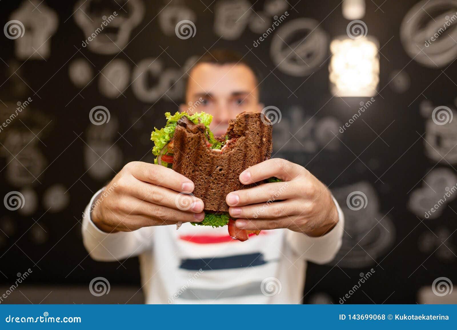 Close-up grappig vaag protrait van jonge mensengreep gebeten sandwich door zijn twee handen Sandwich in nadruk Donkere achtergron