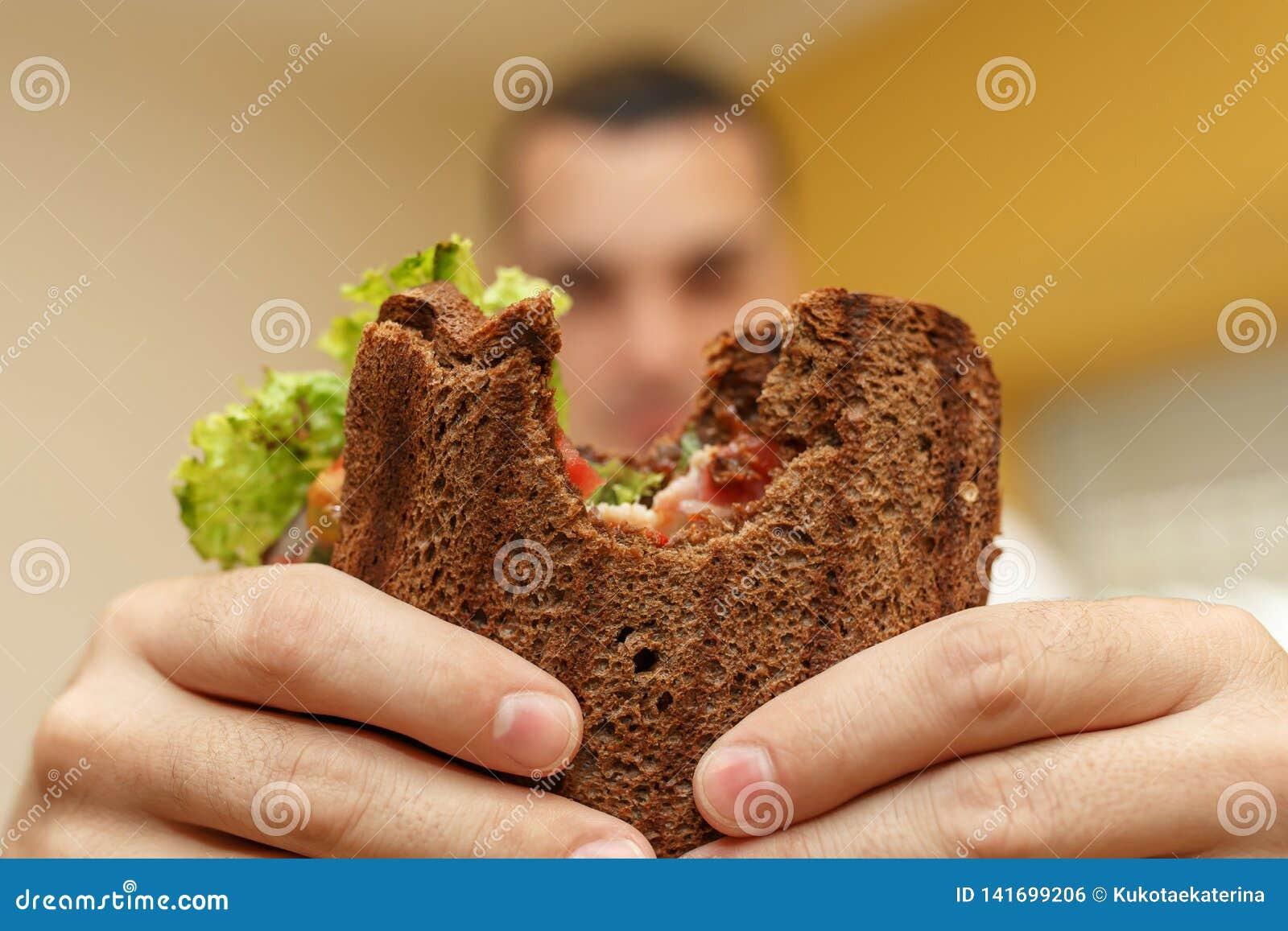 Close-up grappig vaag protrait van jonge mensengreep gebeten sandwich door zijn twee handen Sandwich in nadruk Lichte achtergrond