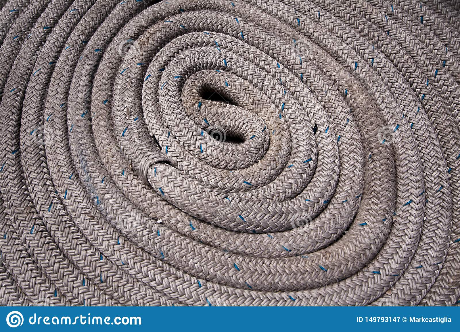 Close up of grey nautical rope coiled and with blue highlights