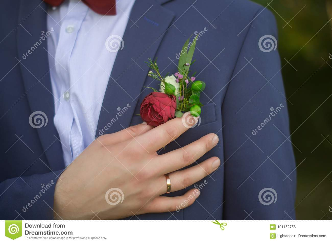 Close up of groom in blue suit and burgundy bow tie adjusting red rose in buttonhole