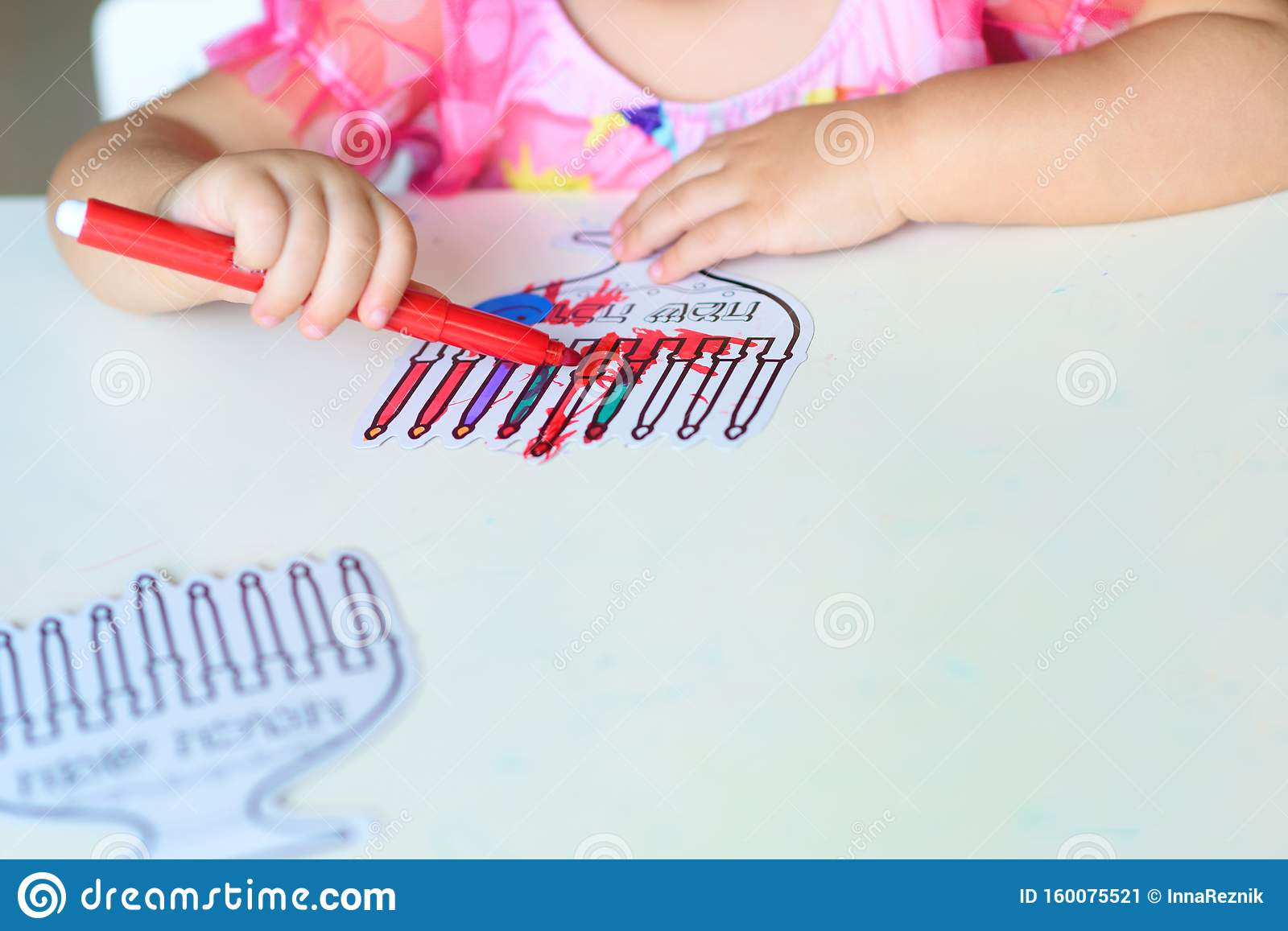 Close up hand cute little toddler kid painting with color pen paper menorah and candle.