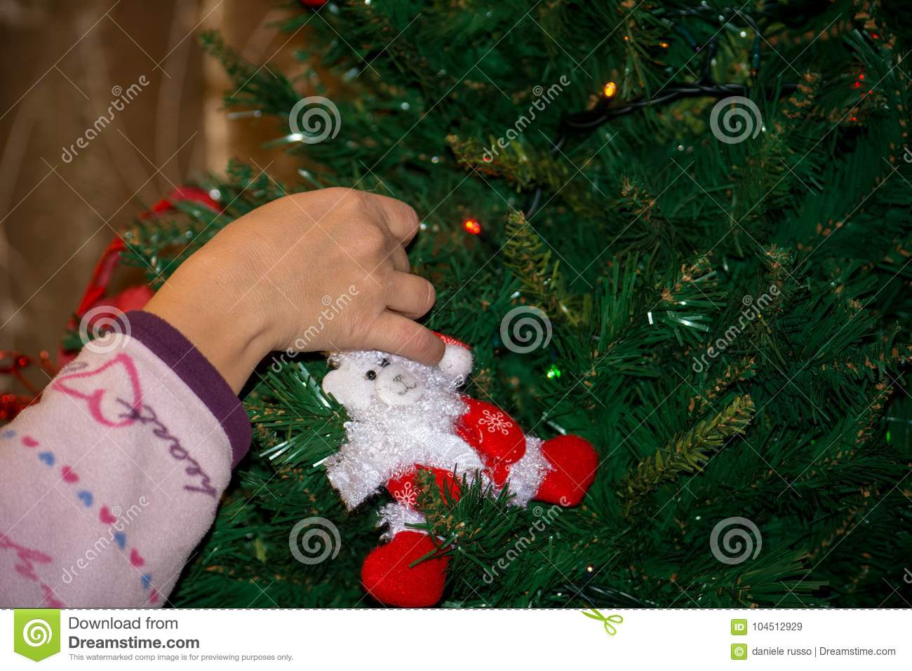 Close Up Of A Hand Dressing The Christmas Tree With
