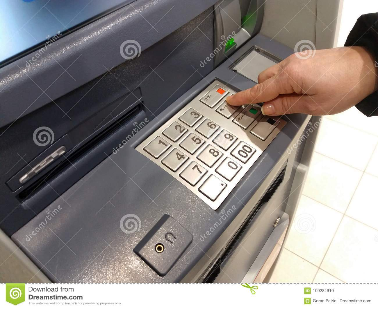 Close-up Of Hand Entering PIN/pass Code On ATM/bank Machine