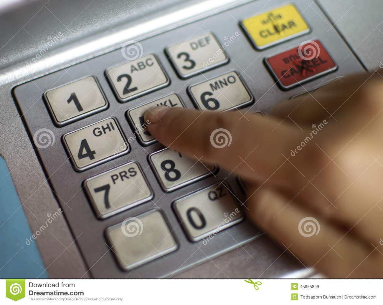 Close-up of hand entering PIN/pass code on ATM/bank machine keypad