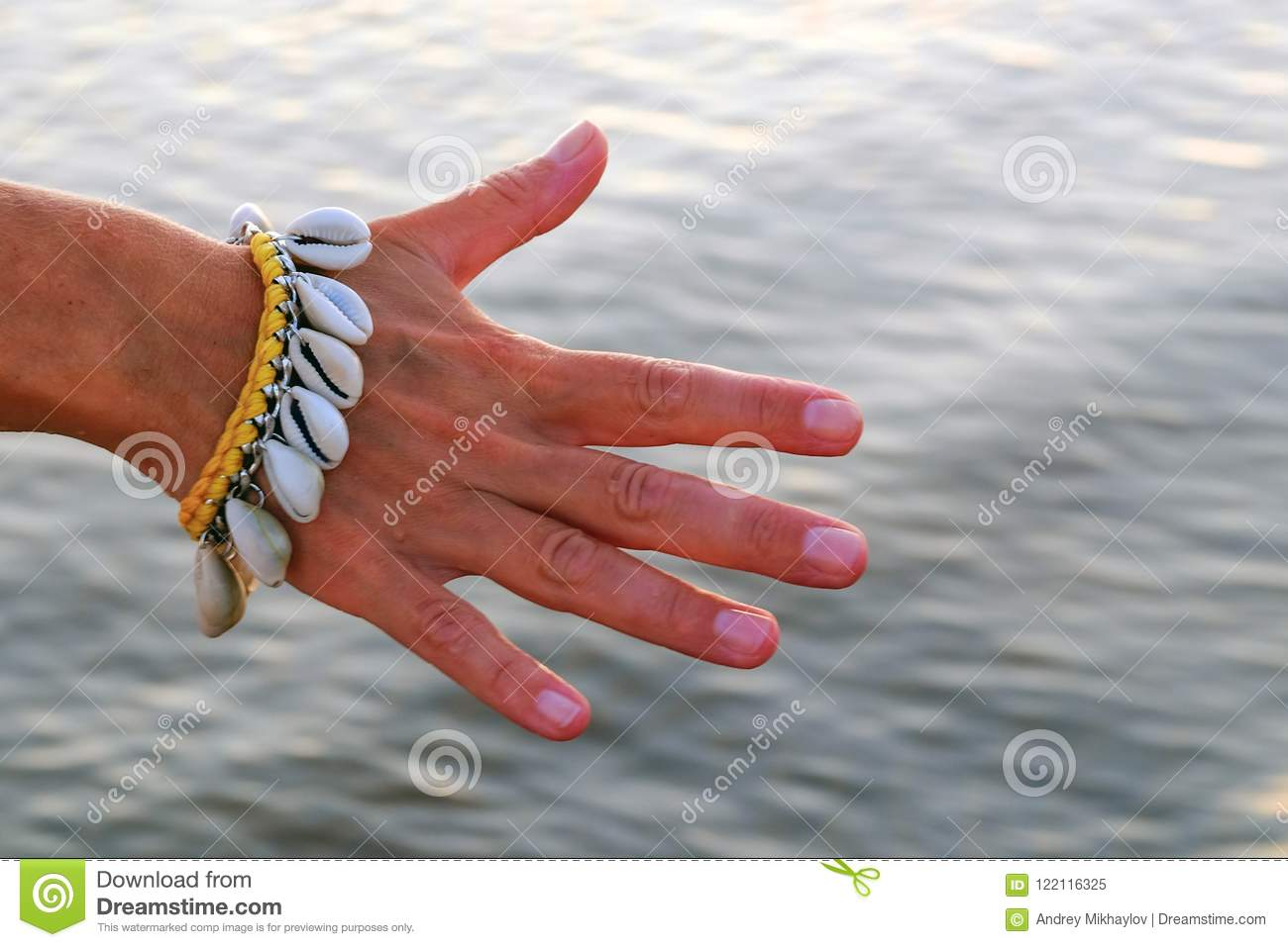 Close-up of the hand of a gentle girl with a bracelet made of seashells. On the background of water.