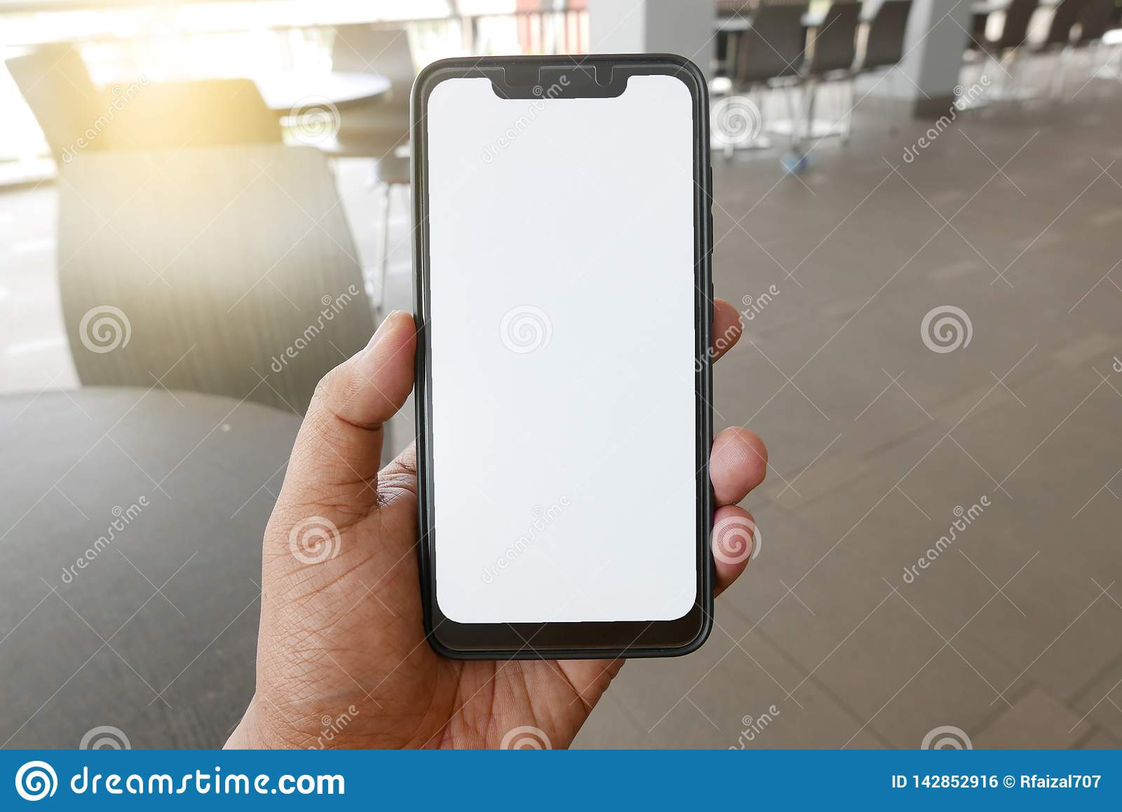Close up of hand holding phone with white screen. Smartphone with mockup on background of cafeteria or restaurant