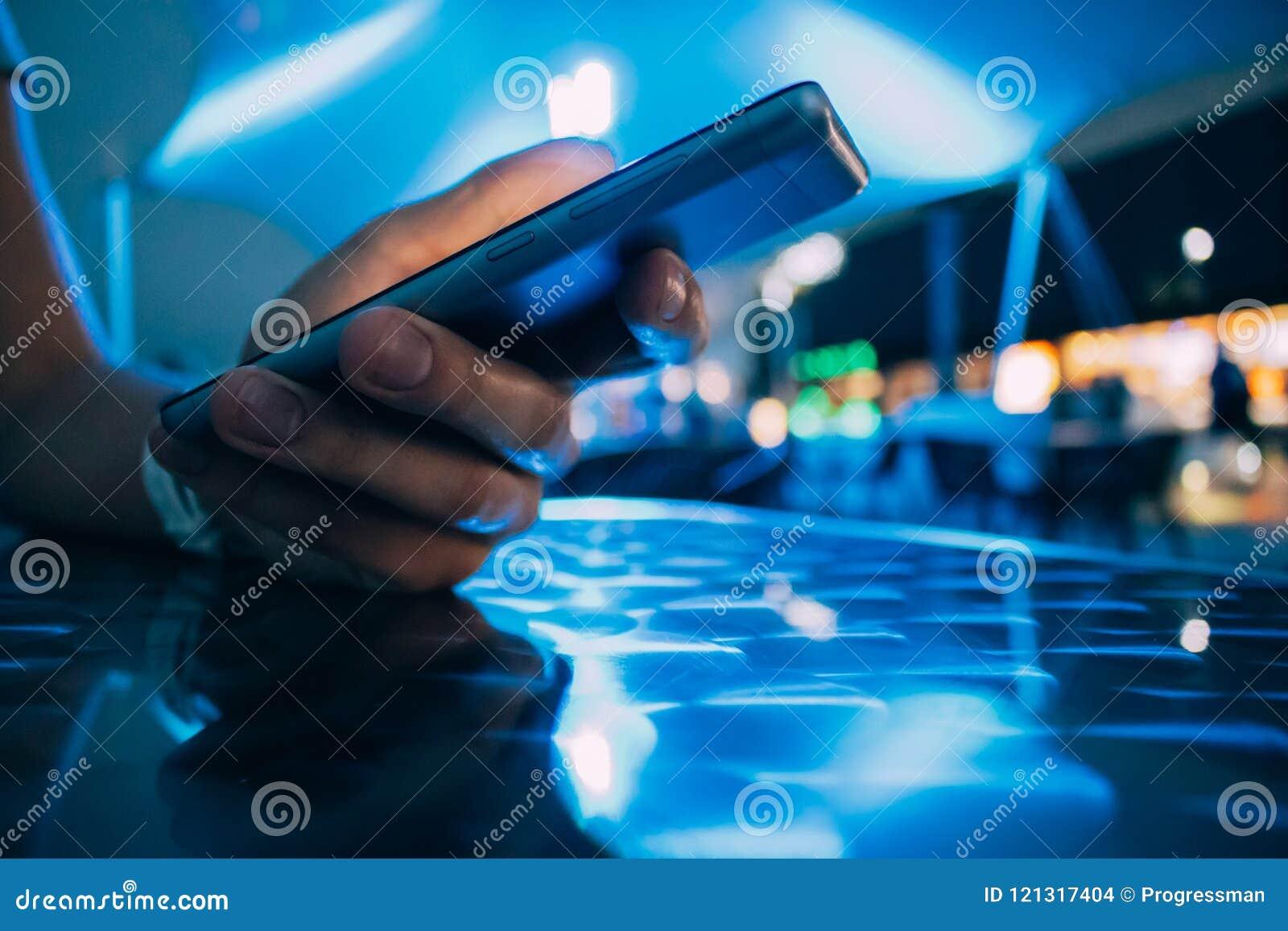 Close-up hand holding smart phone on night bar