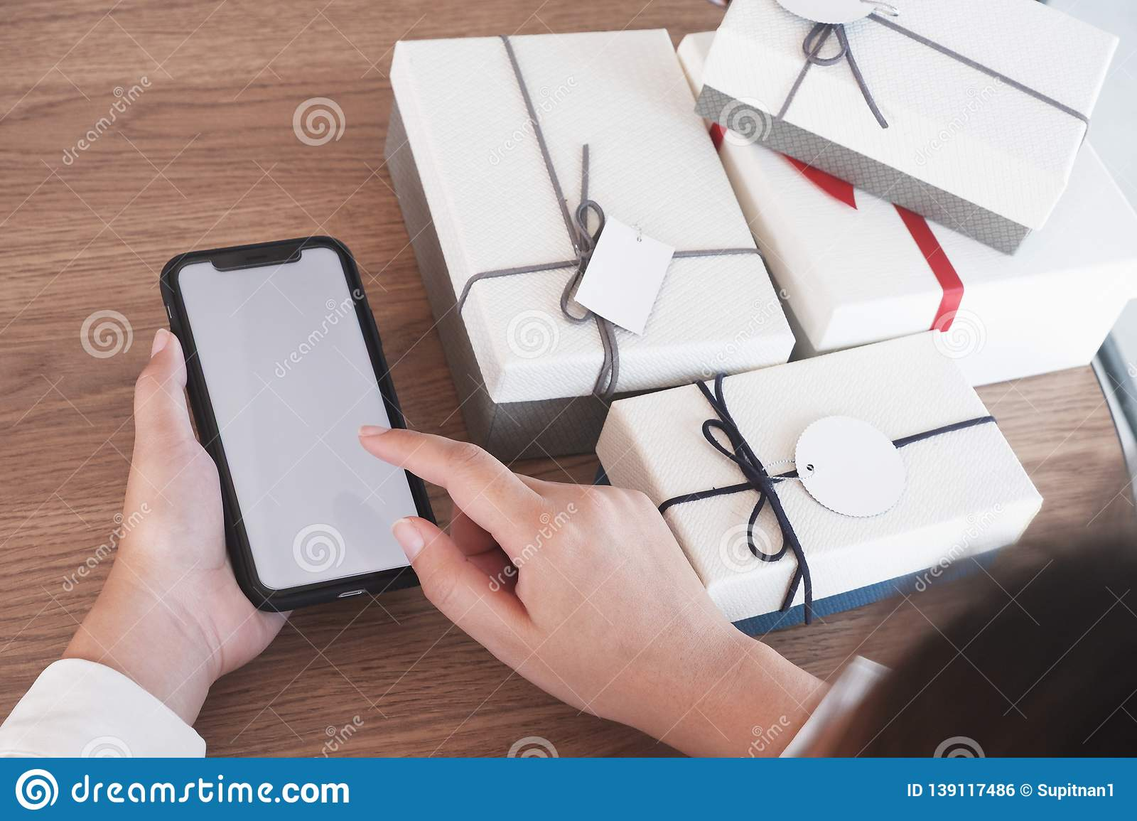 Close-up hand using smartphone for shopping online, gift box on table, shopping for presents