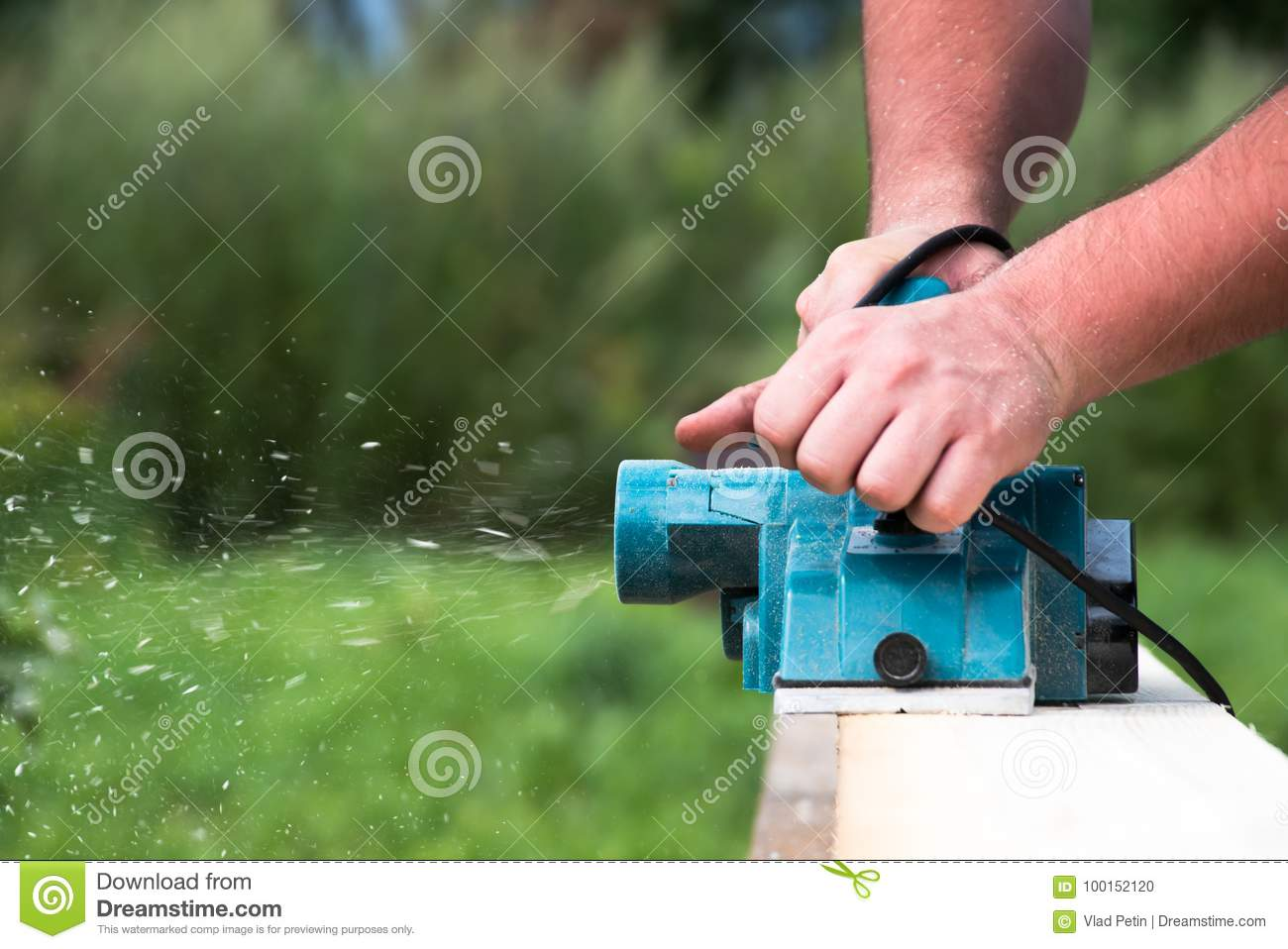 Close up hands of carpenter working with electric planer on wooden plank