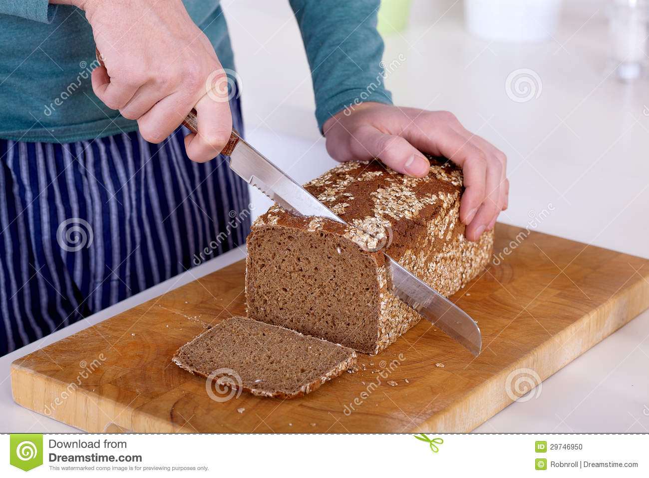 Close Up Of Hands Cutting A Slice Of Bread Stock Photo