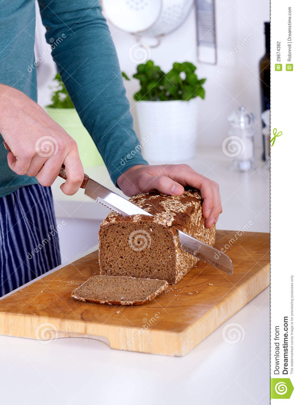 Close Up Of Hands Cutting A Slice Of Bread Stock