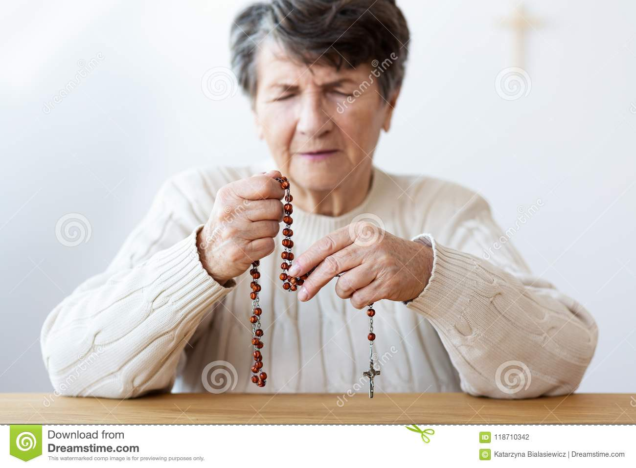 Close-up on the hands of a focused grandmother praying with a re