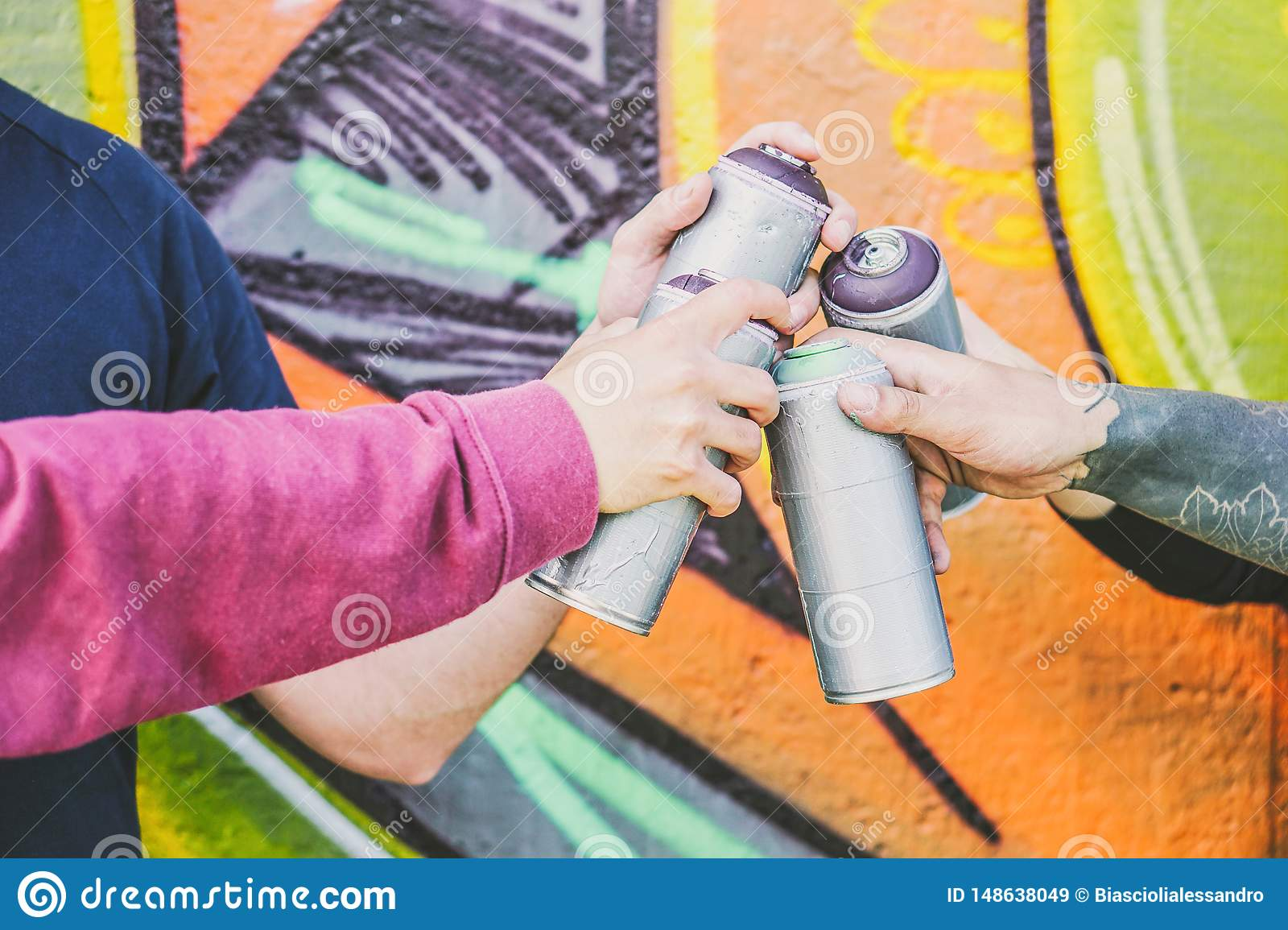 Close up hands of people holding color spray cans against the graffiti wall - Graffiti artists at work