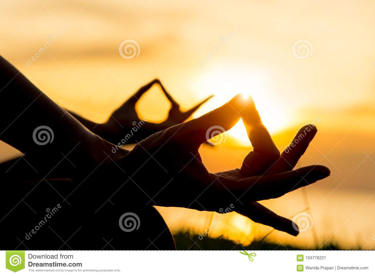 Close up hands. Woman do yoga outdoor. Woman exercising vital and meditation for fitness lifestyle in the beach sunset background
