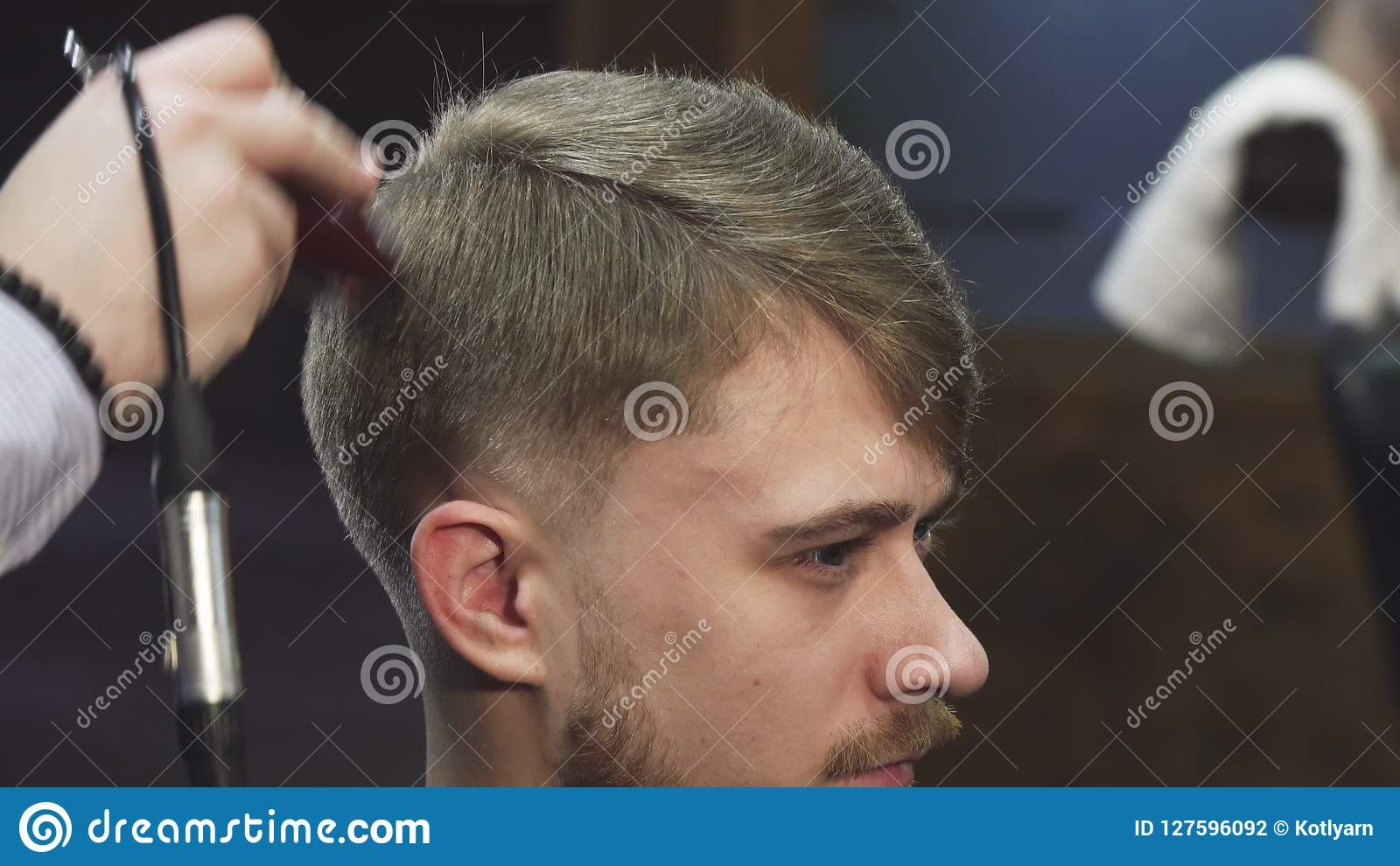 Close up of a handsome yougn man getting a haircut at the barbershop