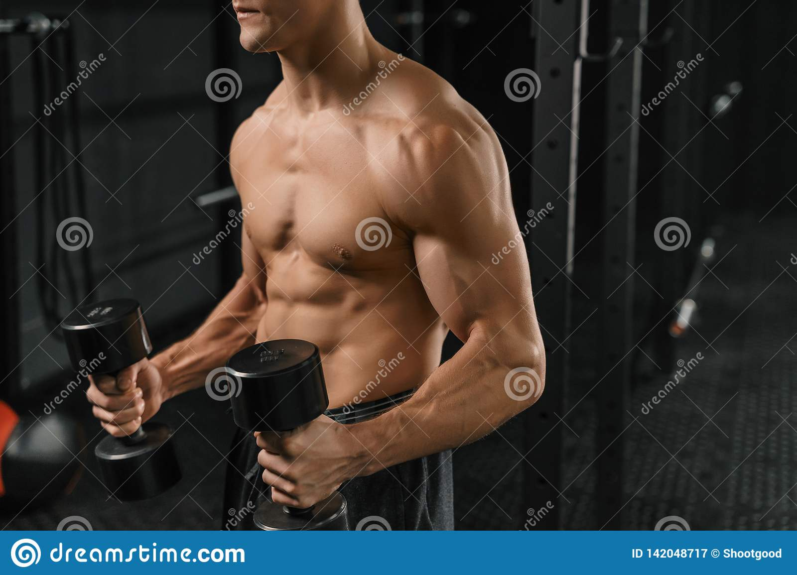 Close-up of a handsome young man lifting dumbbell