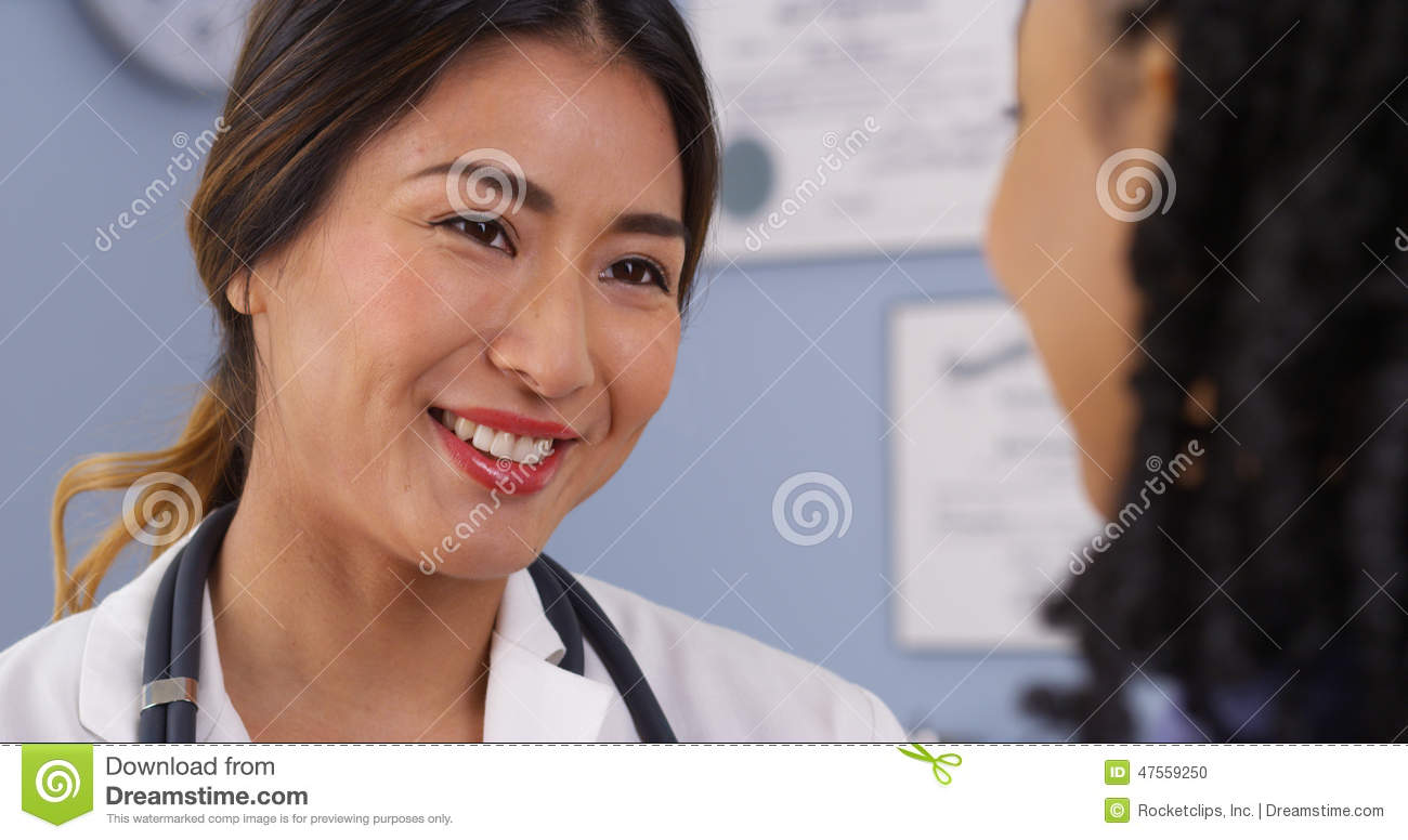 Close up of happy Asian doctor looking at patient