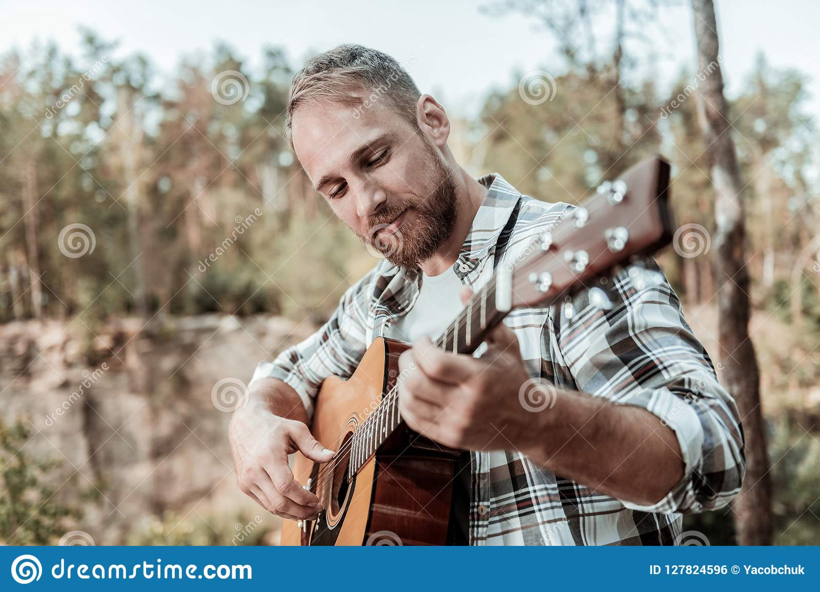 Close up of happy handsome bearded man playing the guitar sitting near mountains