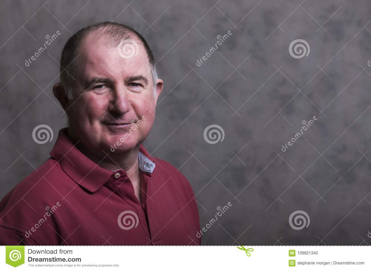 Close up of a happy mature man on a grey background