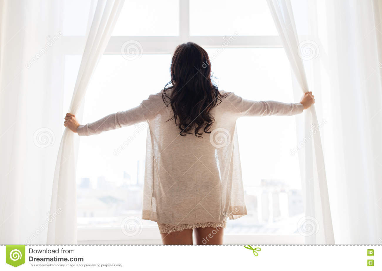 Close up of happy woman opening window curtains stock for Curtains for young adults