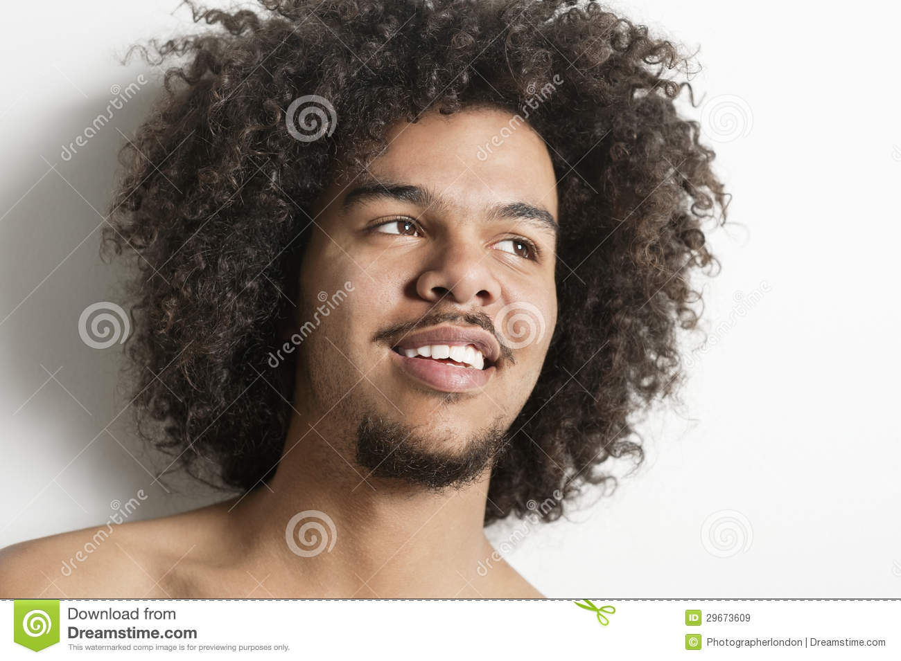 Close Up Of A Happy Young Man With Curly Hair Looking Away