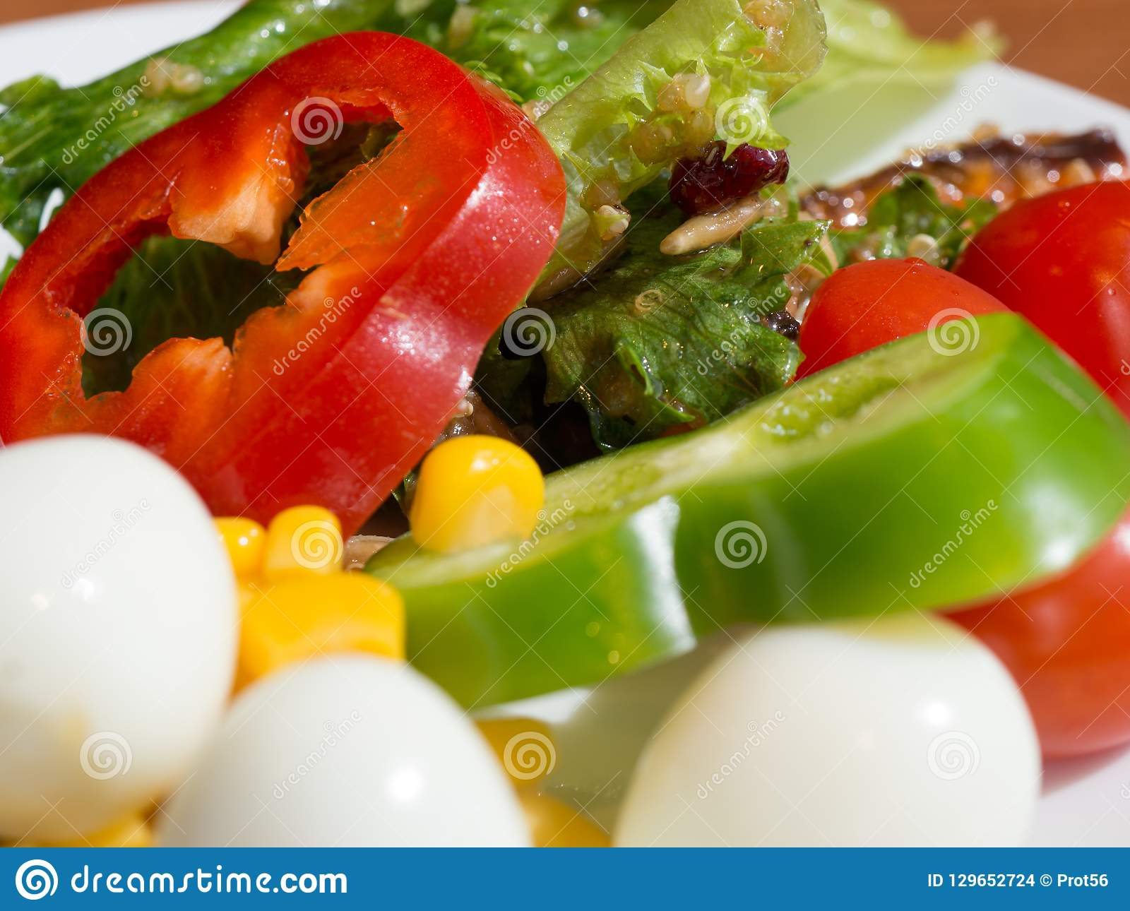 Close up of healthy fresh vegetable salad. colorful vegetable salad. Yellow corn, Green beans, Red tomatoes and Bell pepper, Quail