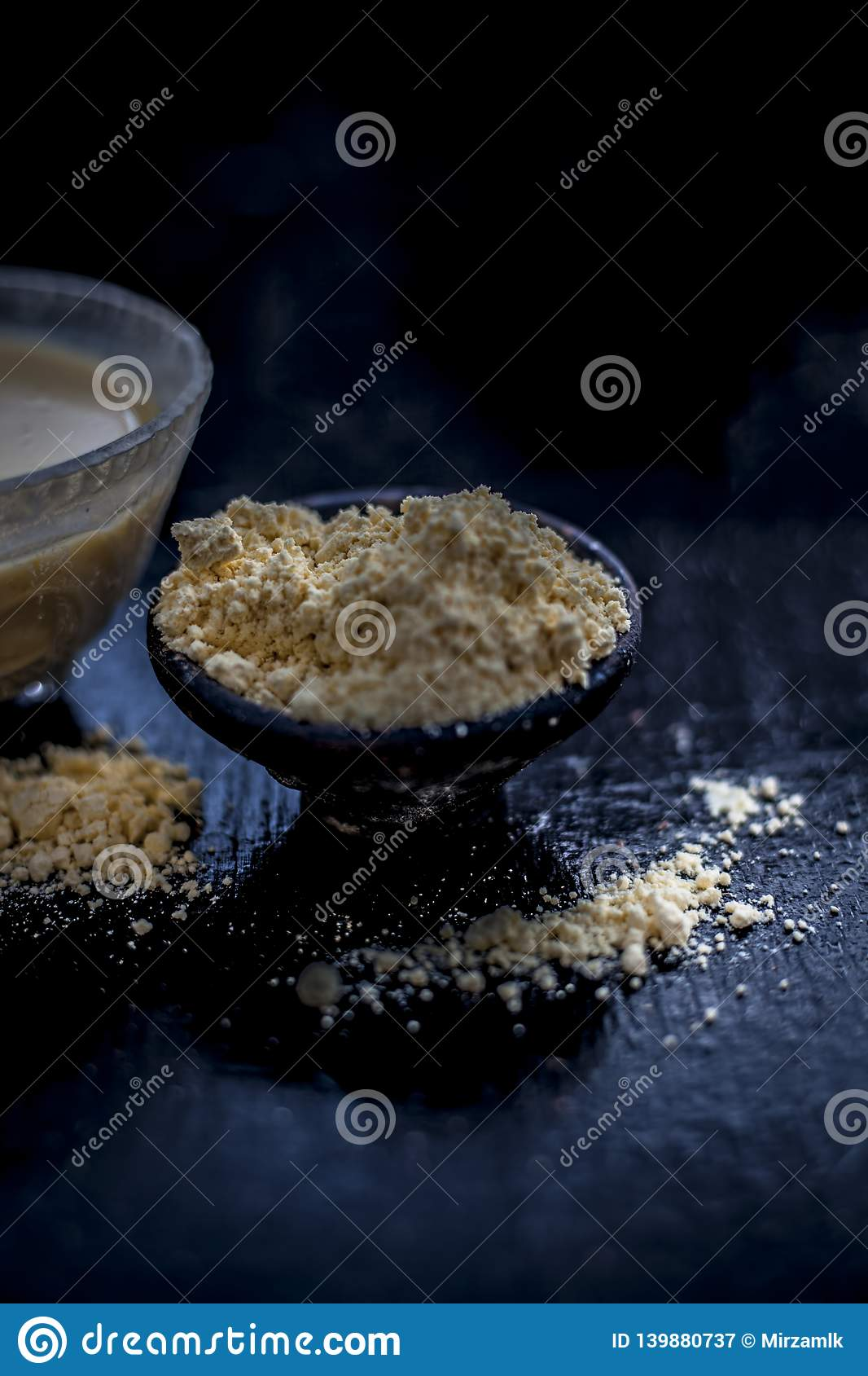 Close up of herbal remedy for hair related problems mainly hair fall on wooden surface i.e. Gram flour with curd and water in a
