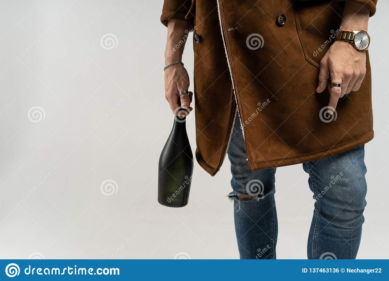 Close up of hipster man in a brown jacket and blue jeans