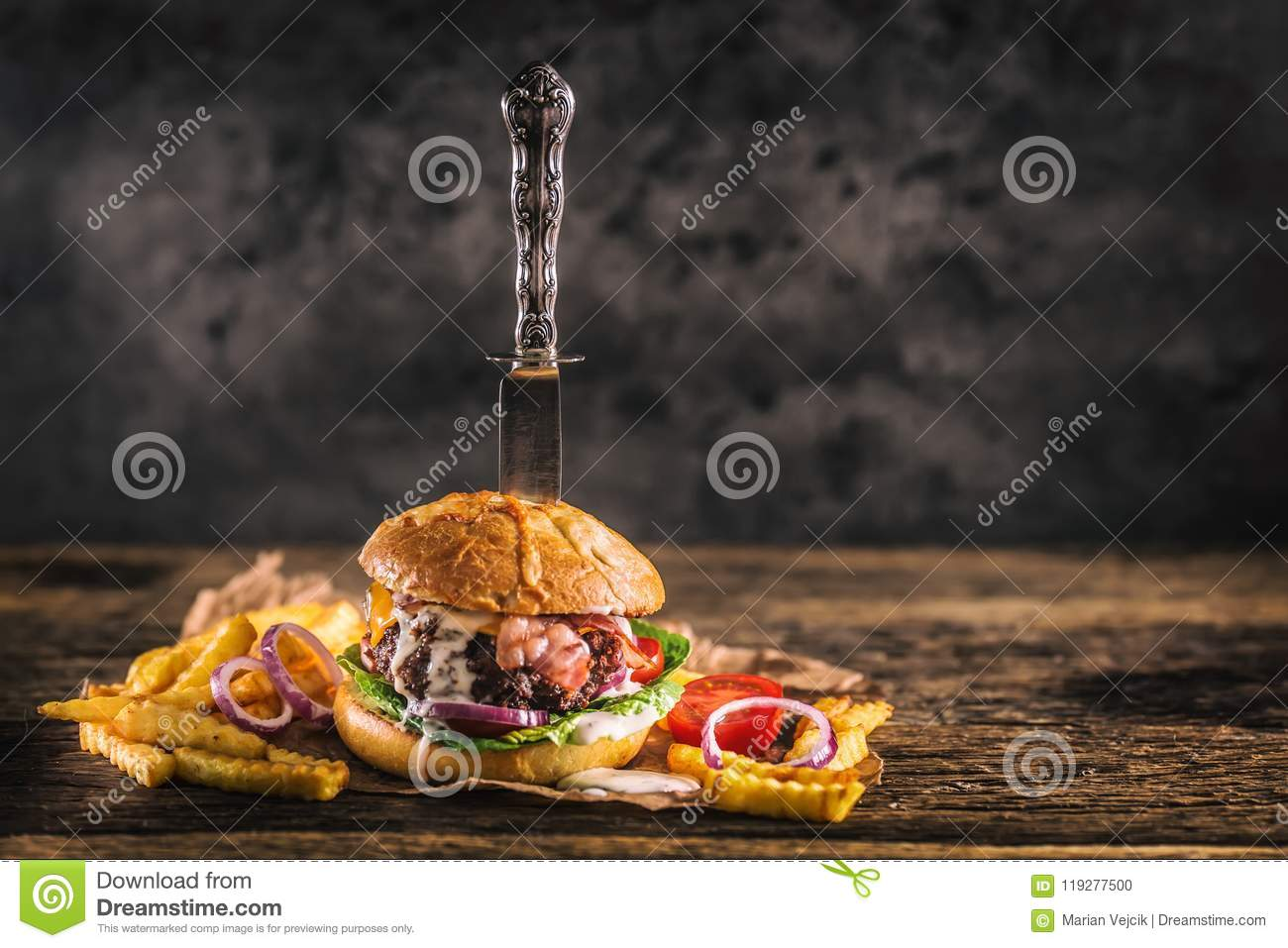 Close-up home made beef burger with knife and fries on wooden ta