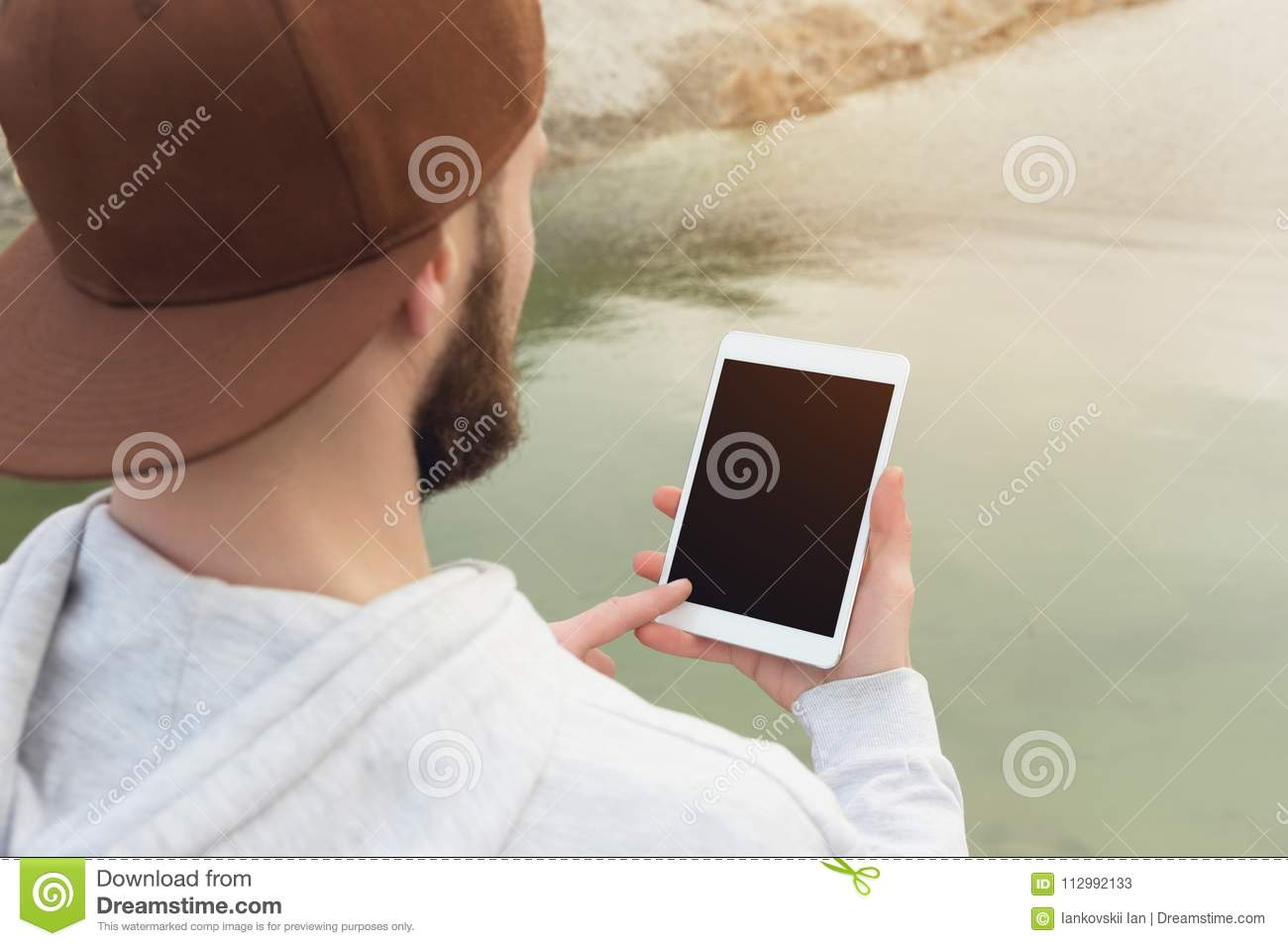 Close-up of a horde in a brown cap in the open air holds a white tablet pc in his hands. A bearded man looks at the