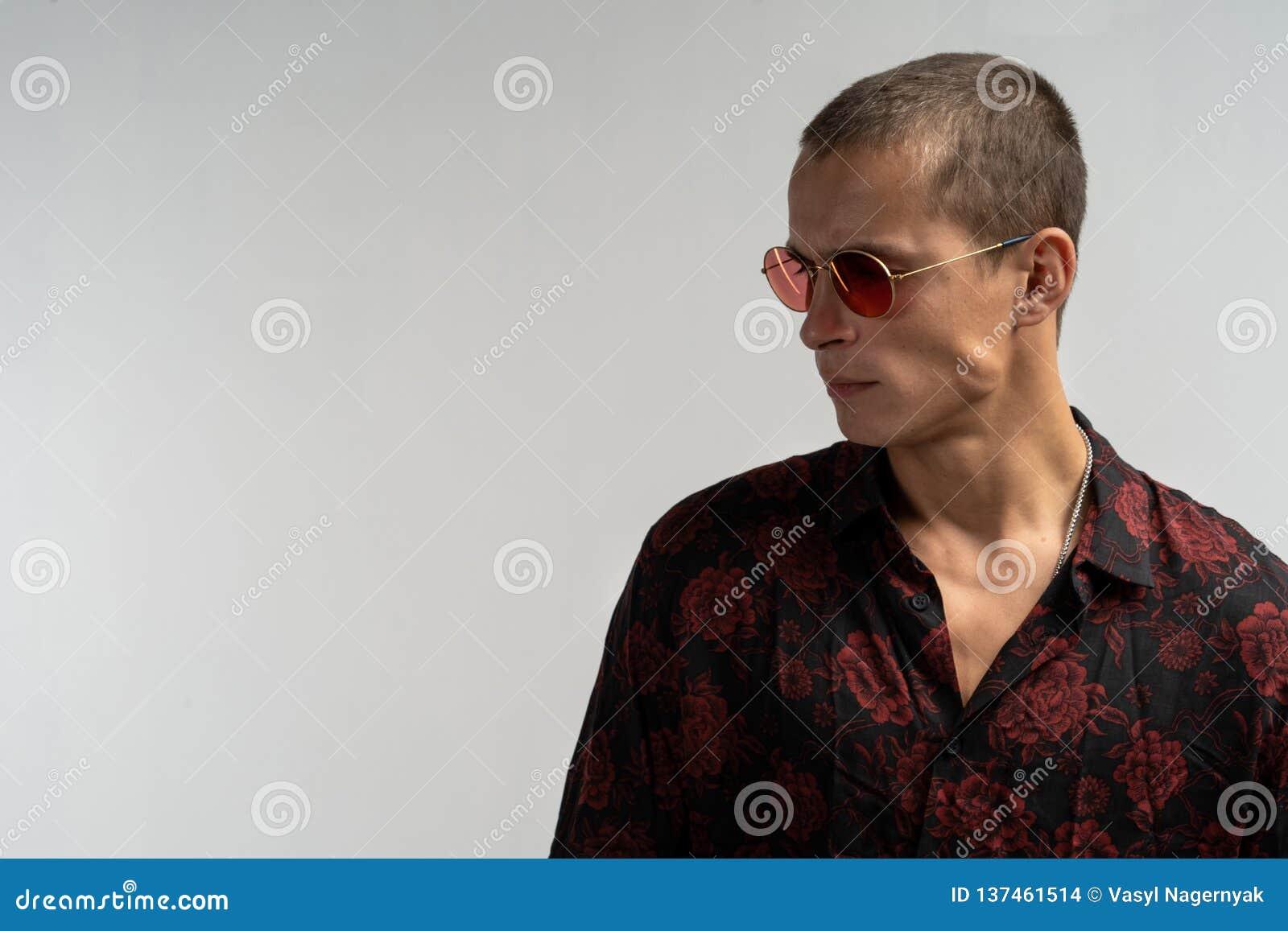 Close-up horizontaal portret die van knap mannelijk model in glazen, onderaan het stellen tegen de witte achtergrond van de studi