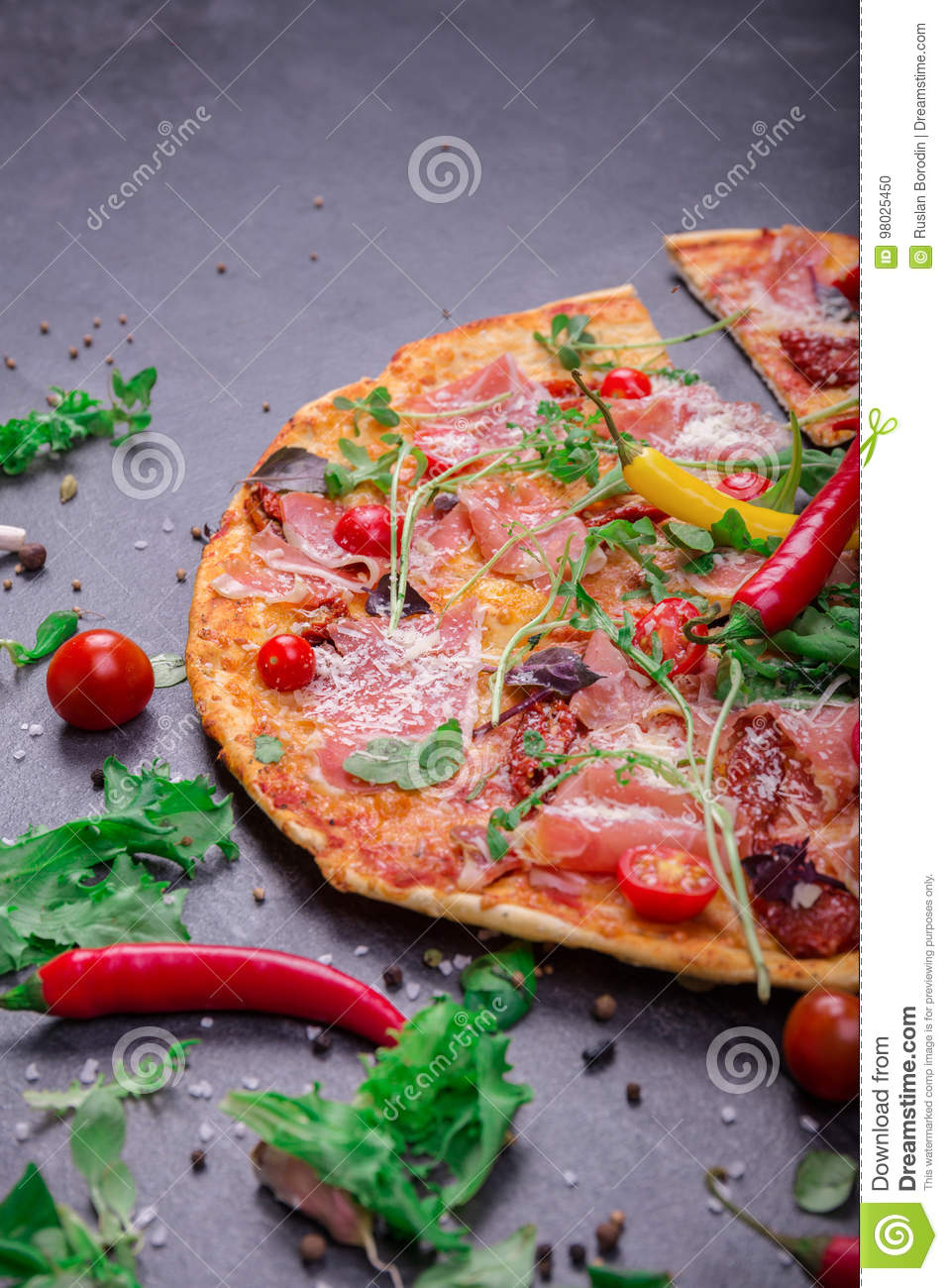 A close-up of hot margarita pizza on a dark background. Cut Italian pizza with vegetables and meat. Copy space.
