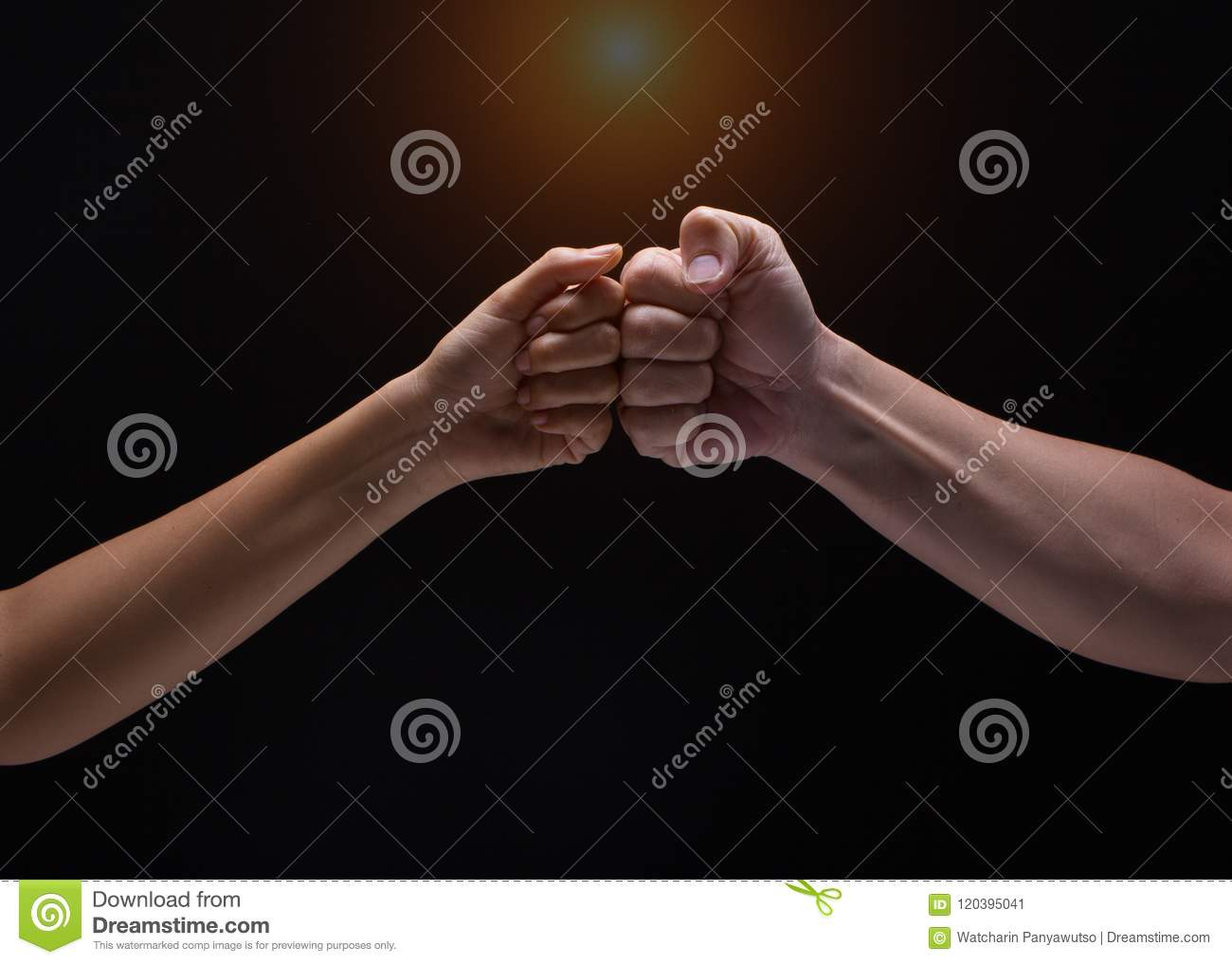 Close up of human hands making a fist bump on black background. a fist pump together after good deal