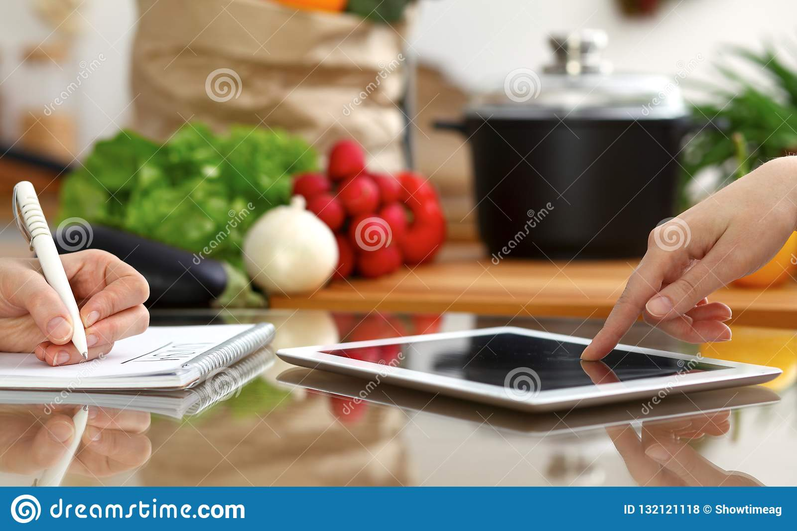 Close-up of human hands using tablet or touch pad. Two women in kitchen.  Cooking 66fc6b6f3a