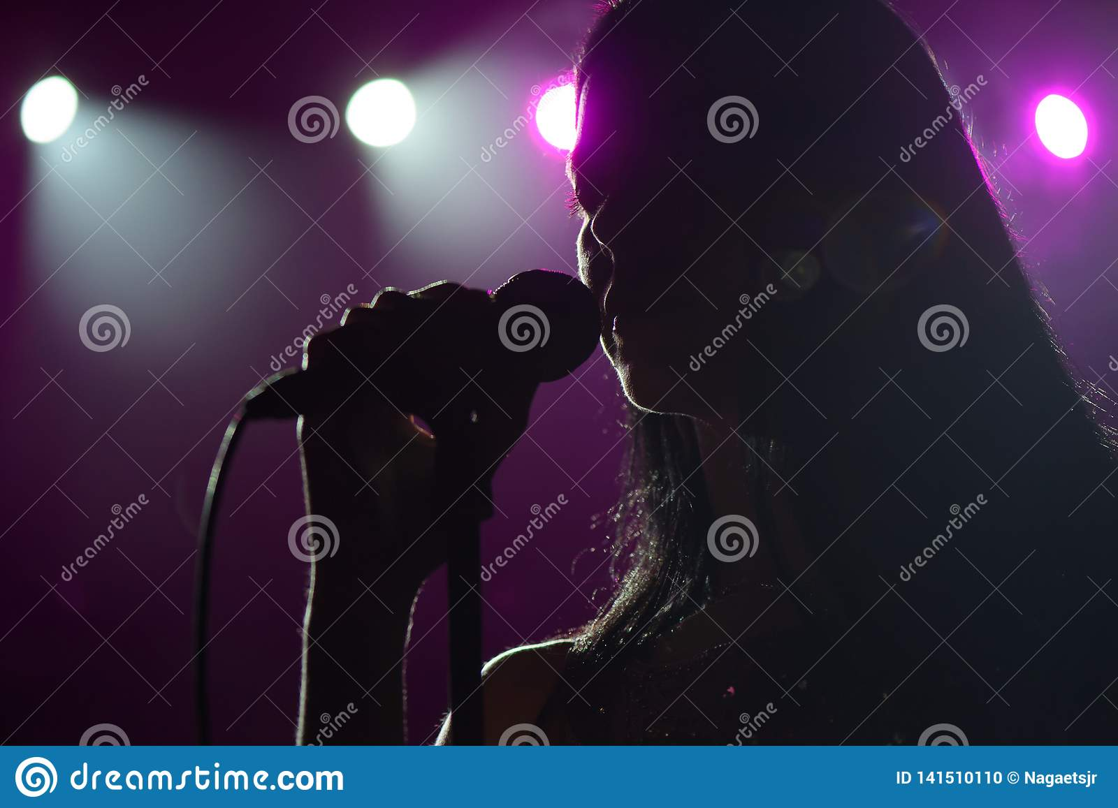 Close up image of live singer on stage. Microphone in hand singer on stage.