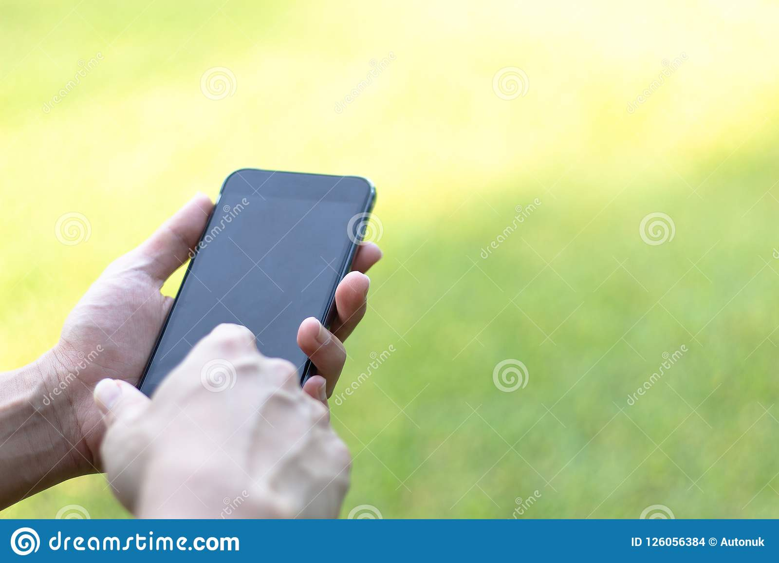Close-up image of male hands using black smartphone in park