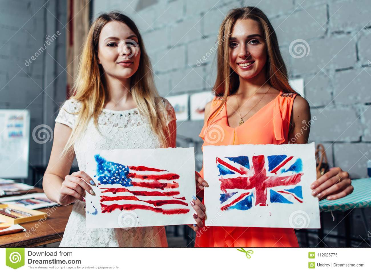 Close-up image of two young women holding a drawing of British and American flags hand-drawn with aquarelle technique on