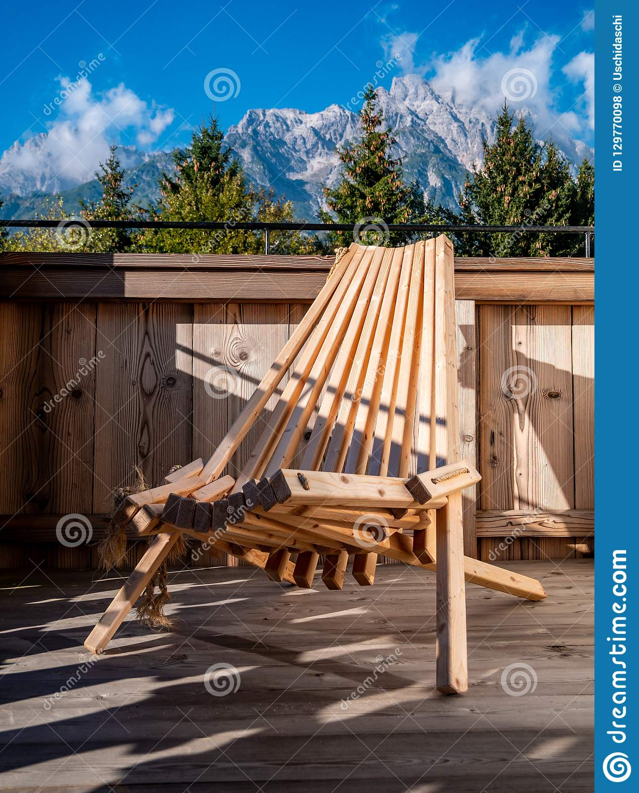 Image of wooden chair on balcony in alpine landscape