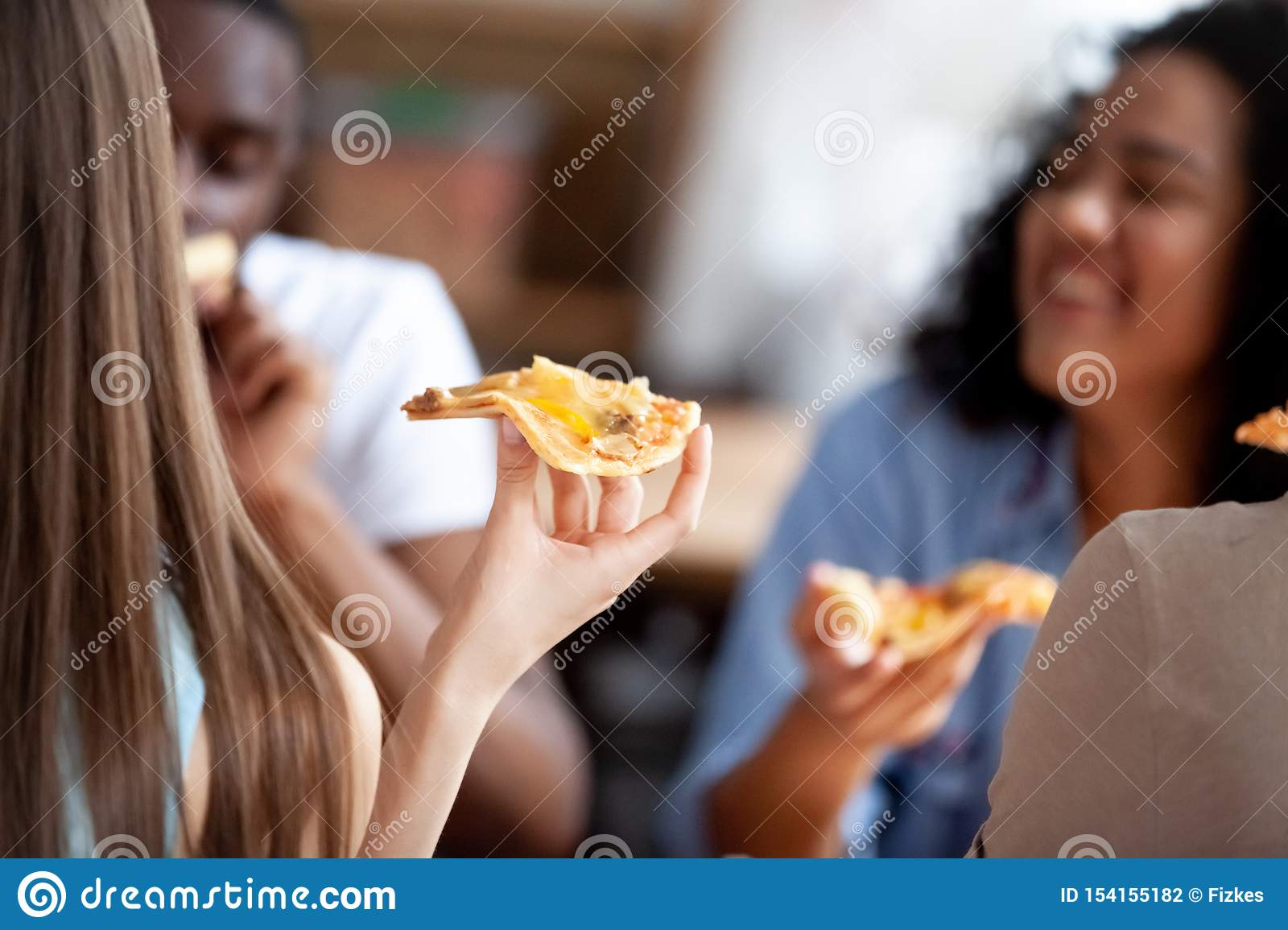 Close up image of young woman holding slice of pizza.